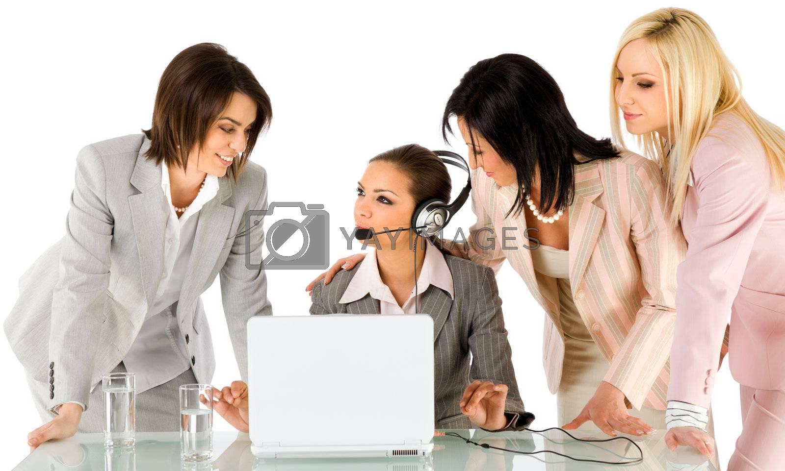 Successful team of four beautiful businesswomen talking behind laptop