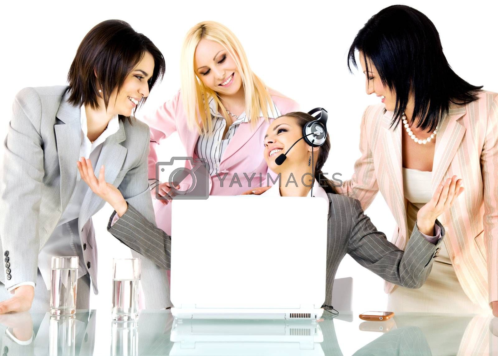 Successful team of four businesswomen smiling behind laptop, one with headset