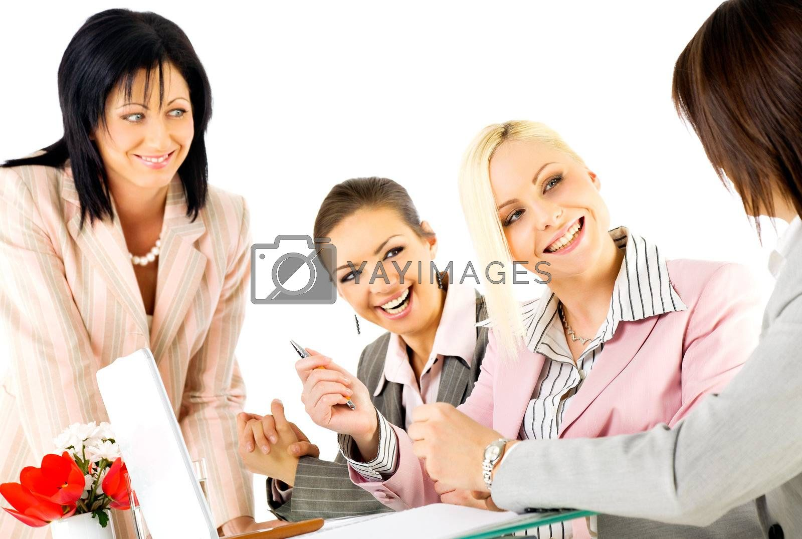 Team of four successful businesswomen working and smiling behind laptop