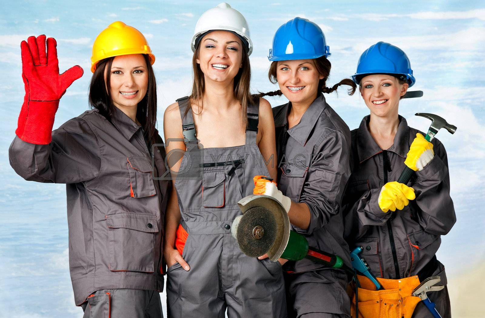 Four happy female construction workers posing with instruments on beach, studio