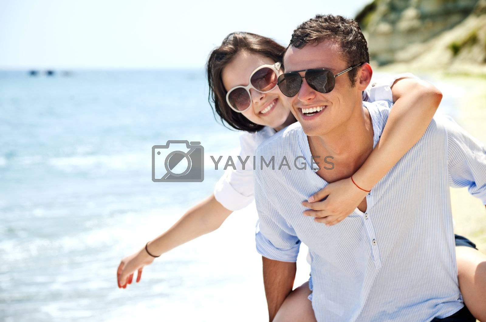 piggyback ride to beautiful female on solitary beach, happy couple