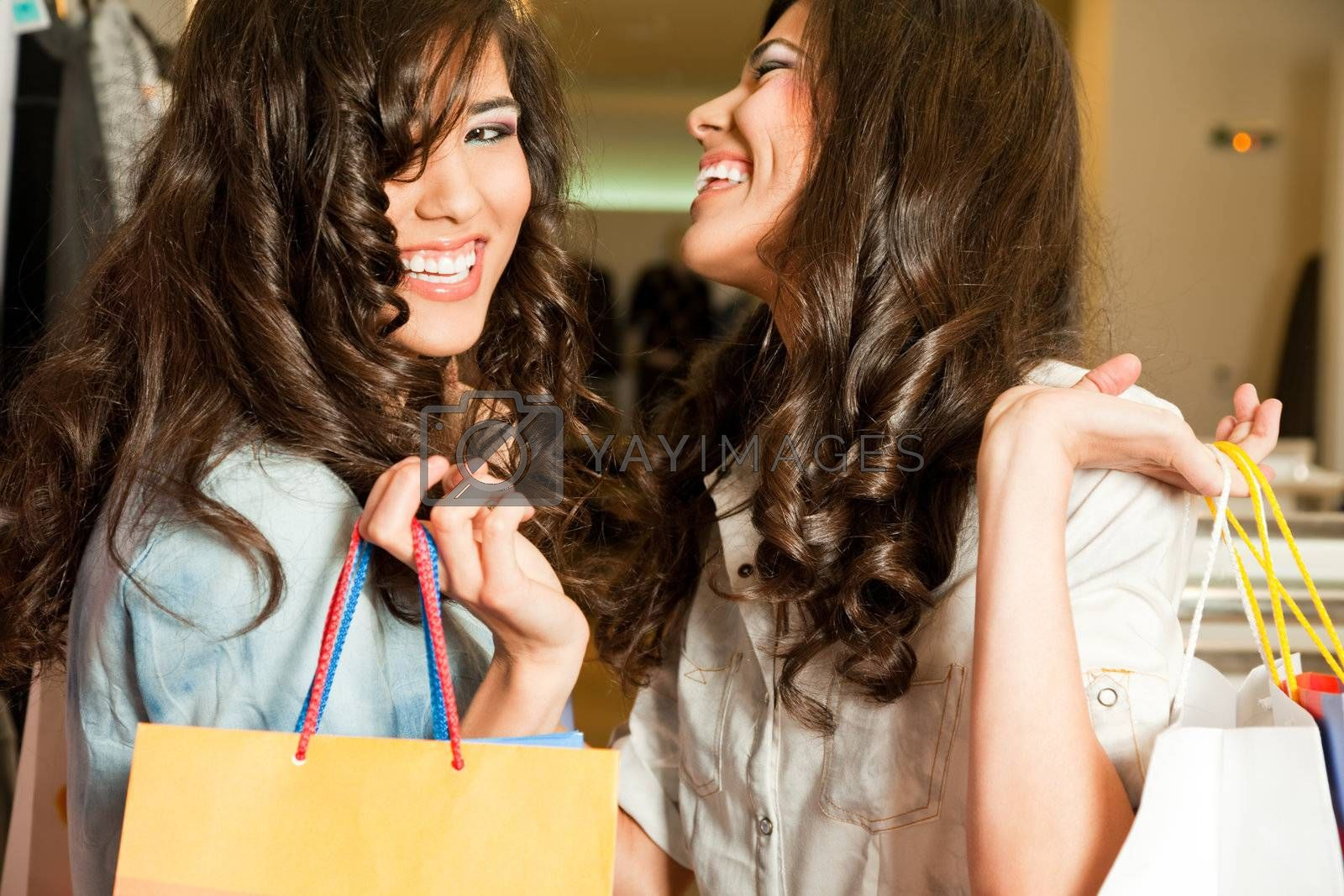 Young beautiful twin girls laughing and holding shopping bags in a store