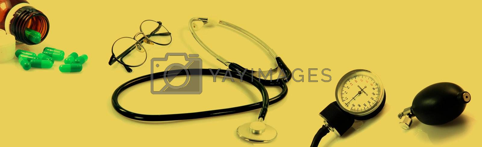 spectacles phonendoscope sphygmomanometer  and botle of pills in dark yellow tind health and medical objects this image is composed from 3 shuts with canon 400 xti