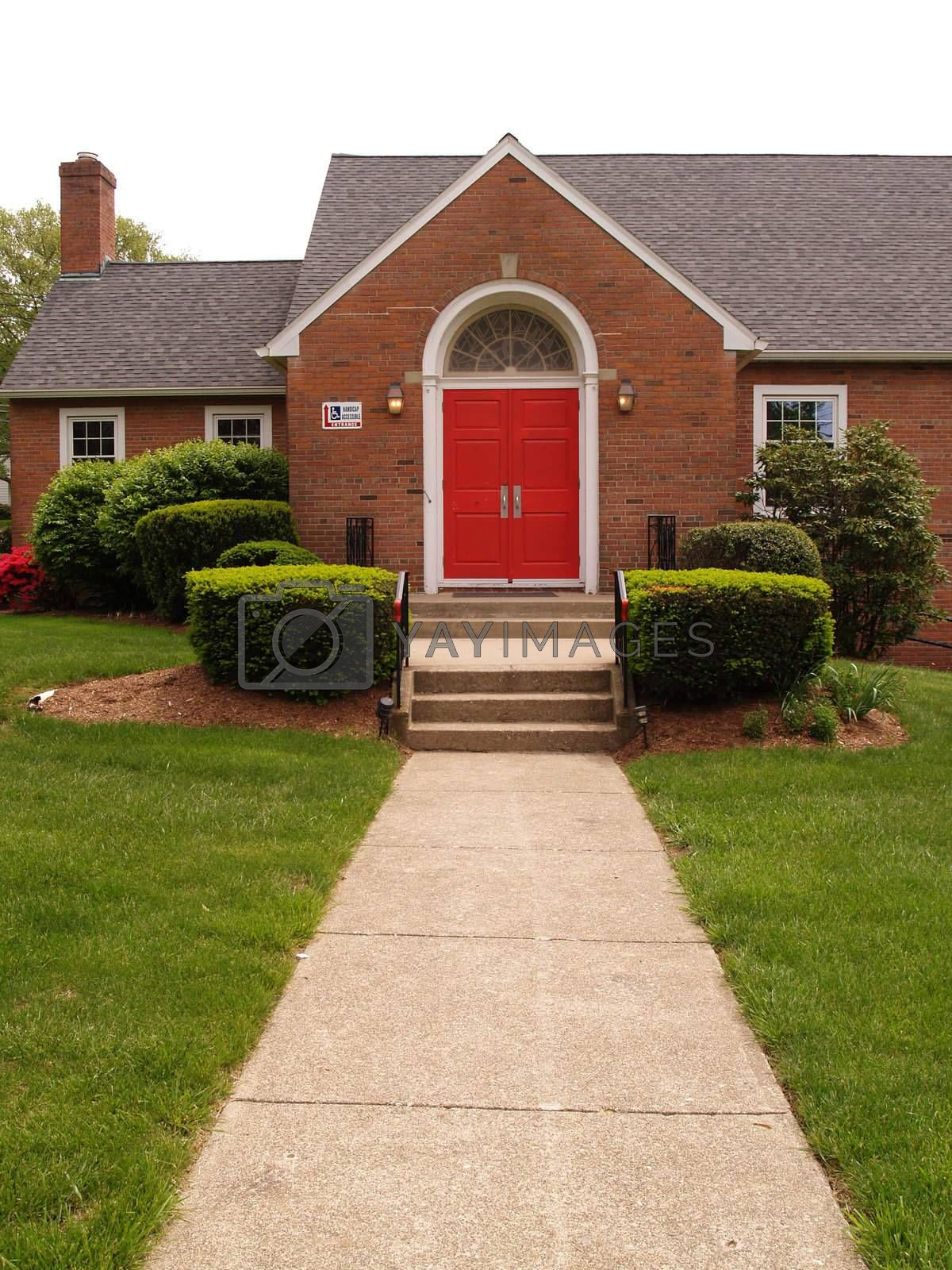 sidewalk leading into a brick rural church with red doors