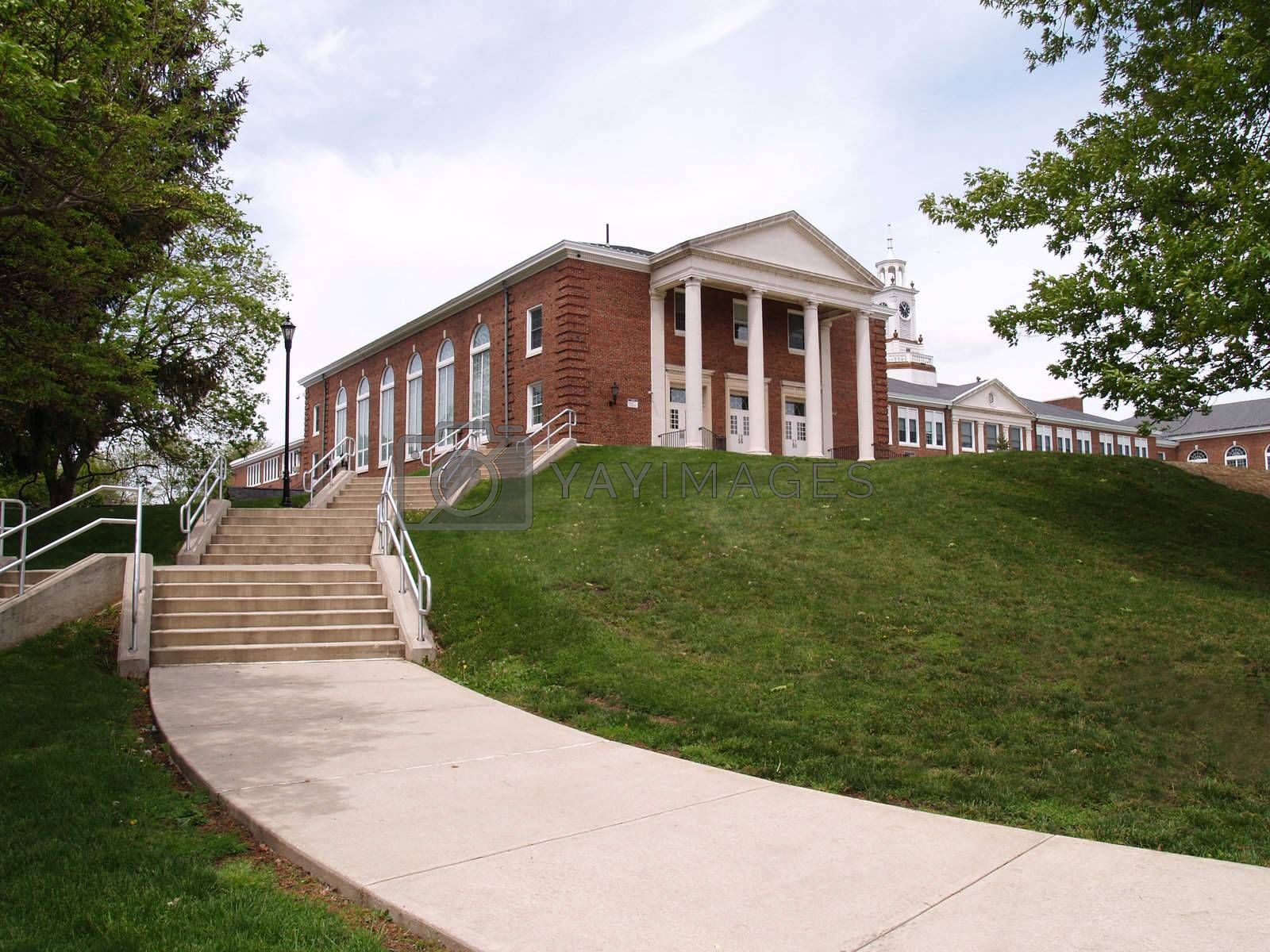 a sidewalk and steps leading to an old high school on a hill