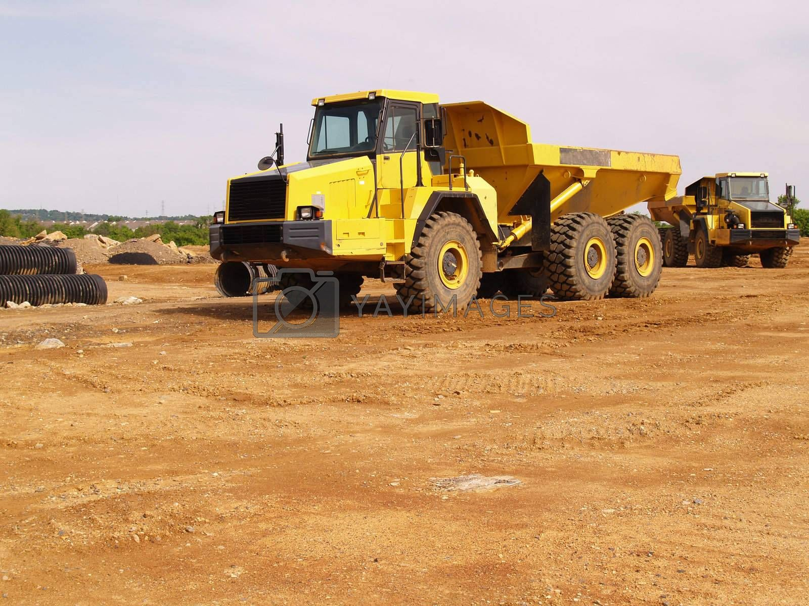 a yellow dump truck by a construction site