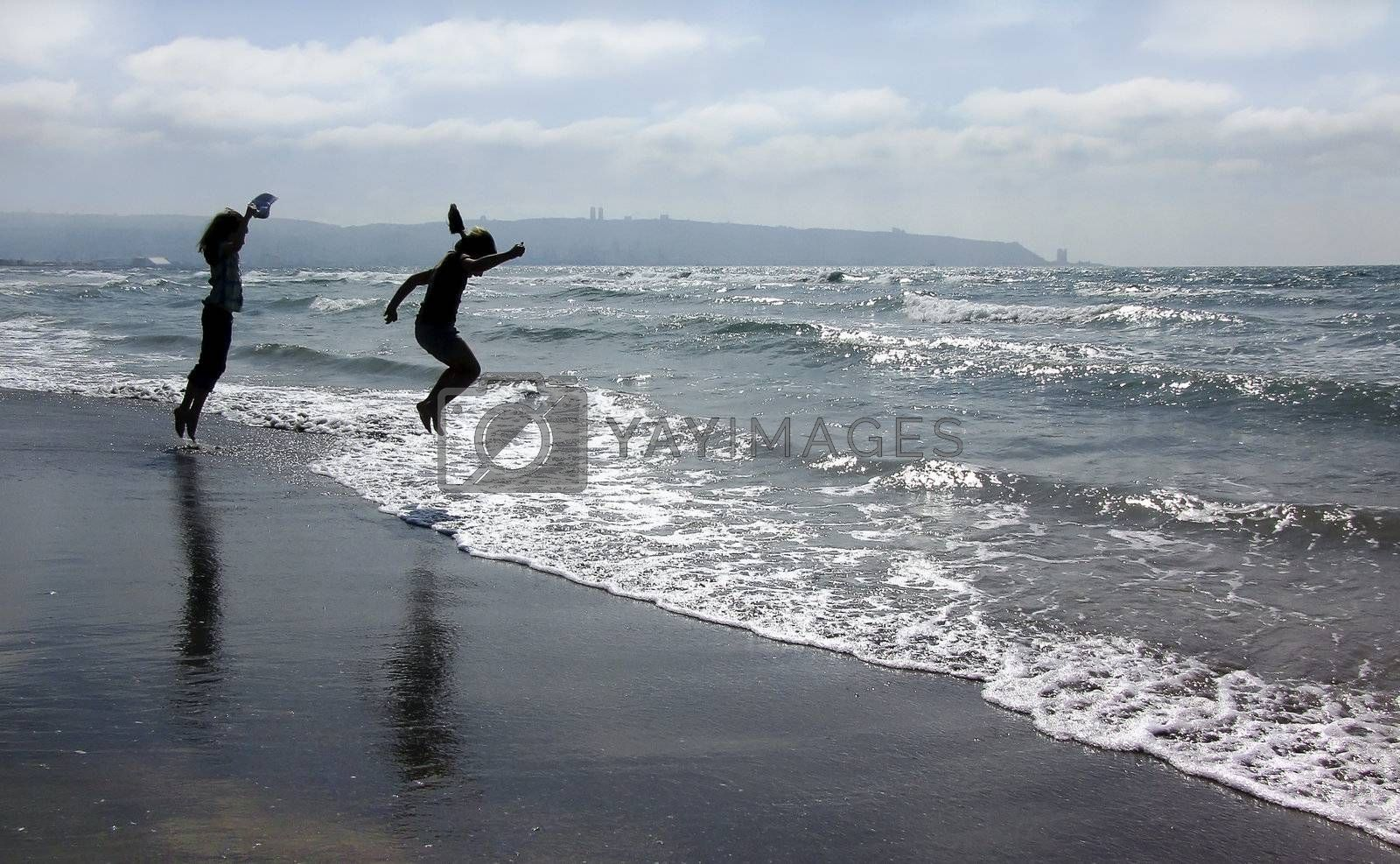 children jumping on the beach        children and the sea