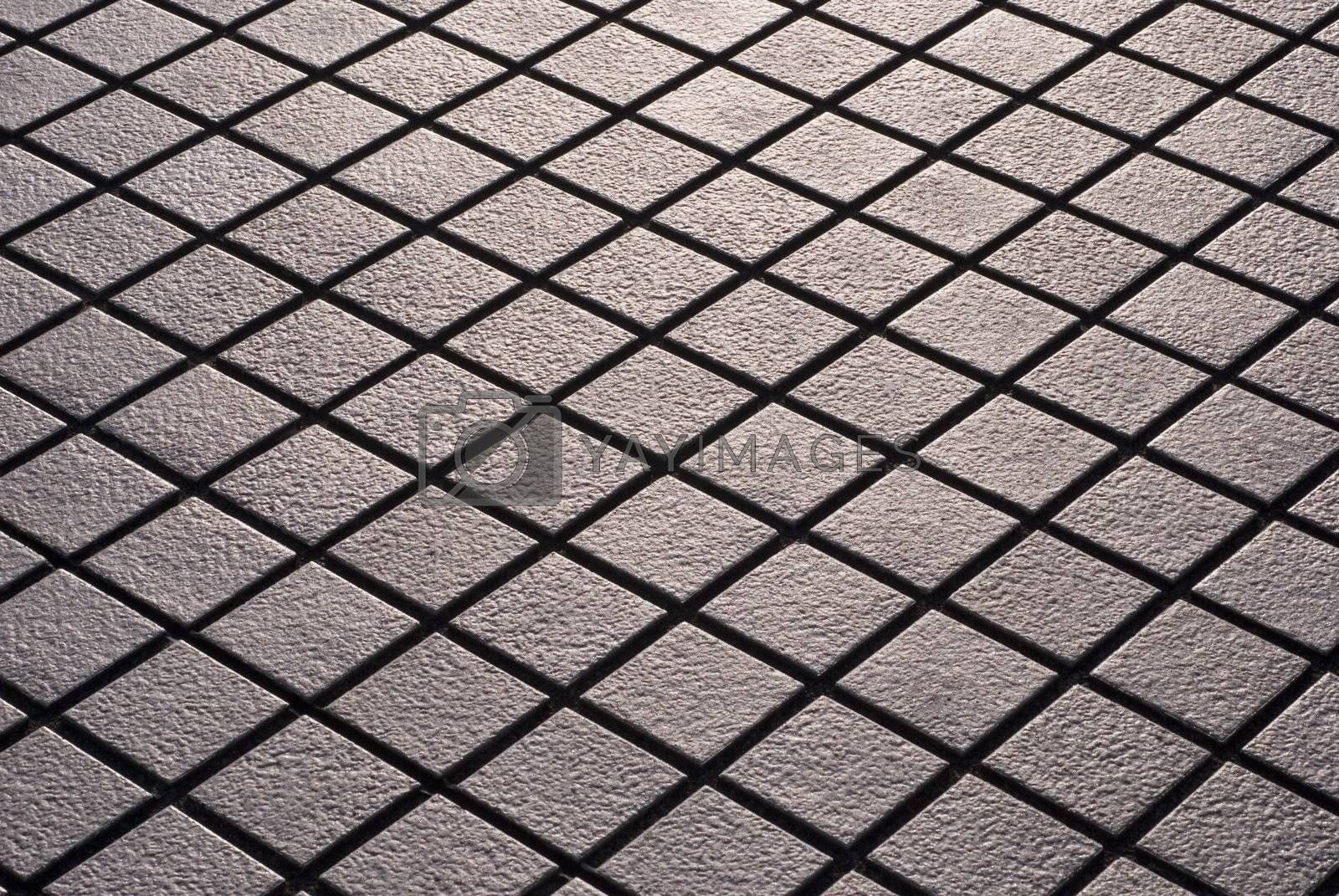 Criss-crossed design of diamond shaped street tiling.