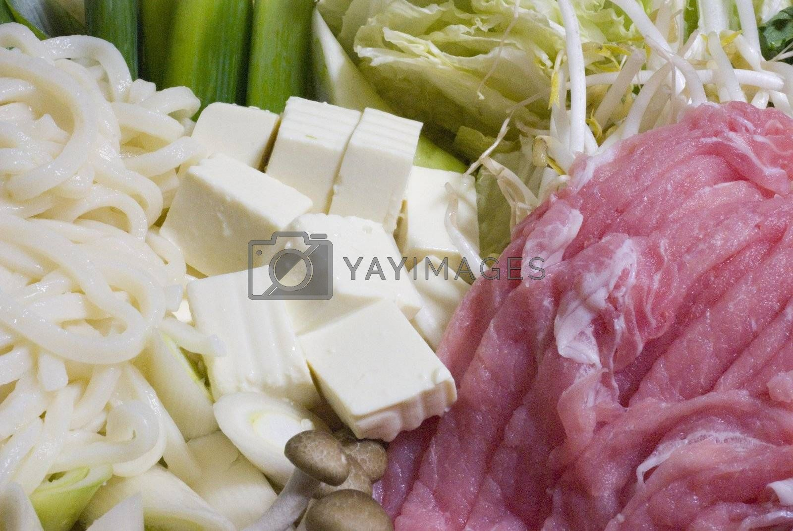 Noodles, tofu, pork and other ingredients spread out prepared for shabu shabu. white and red horizontal