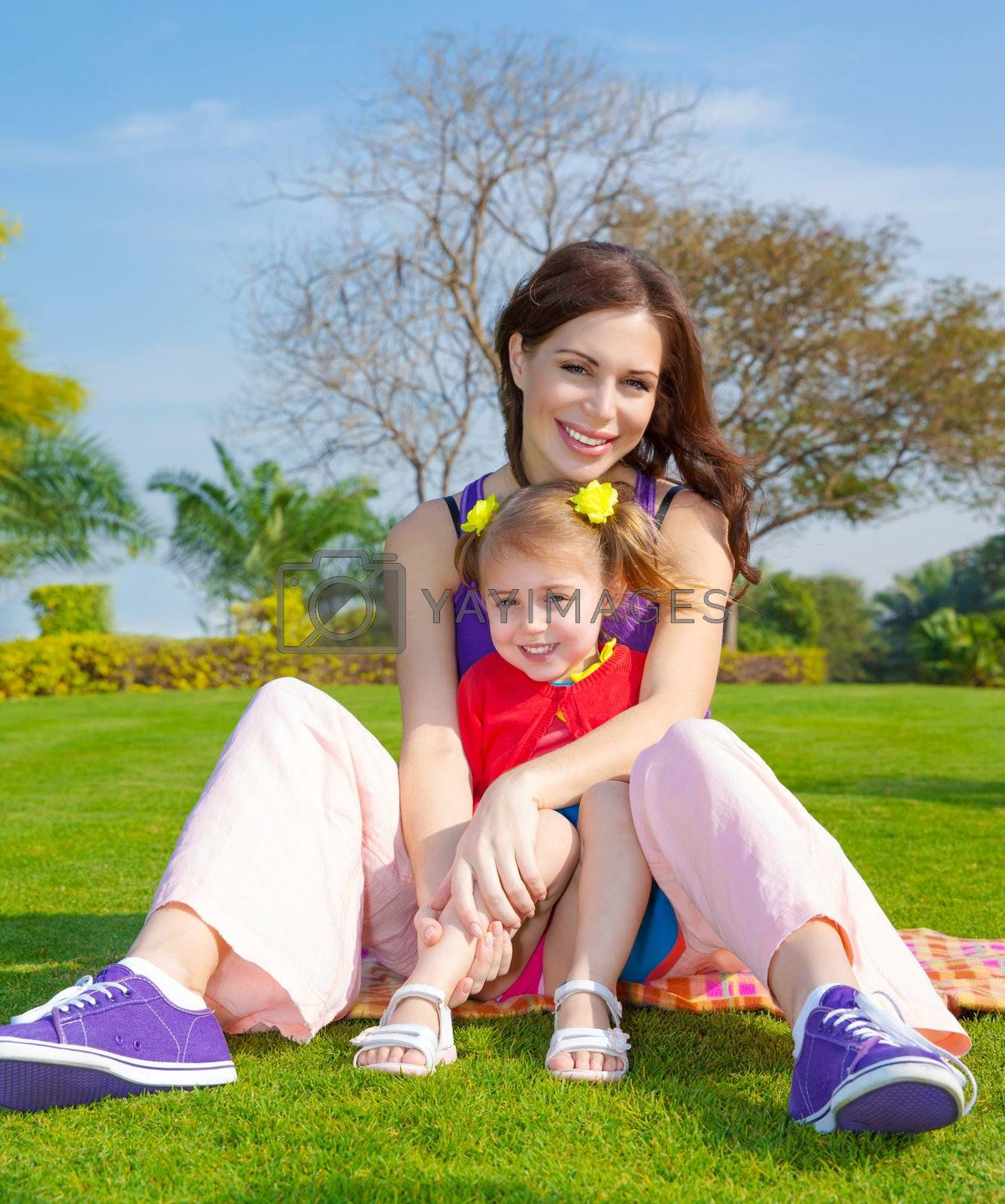 Photo of young mother with cute little daughter sitting down on green grass field in park, beautiful woman with small pretty girl having fun outdoors in spring, happy family on picnic, love concept