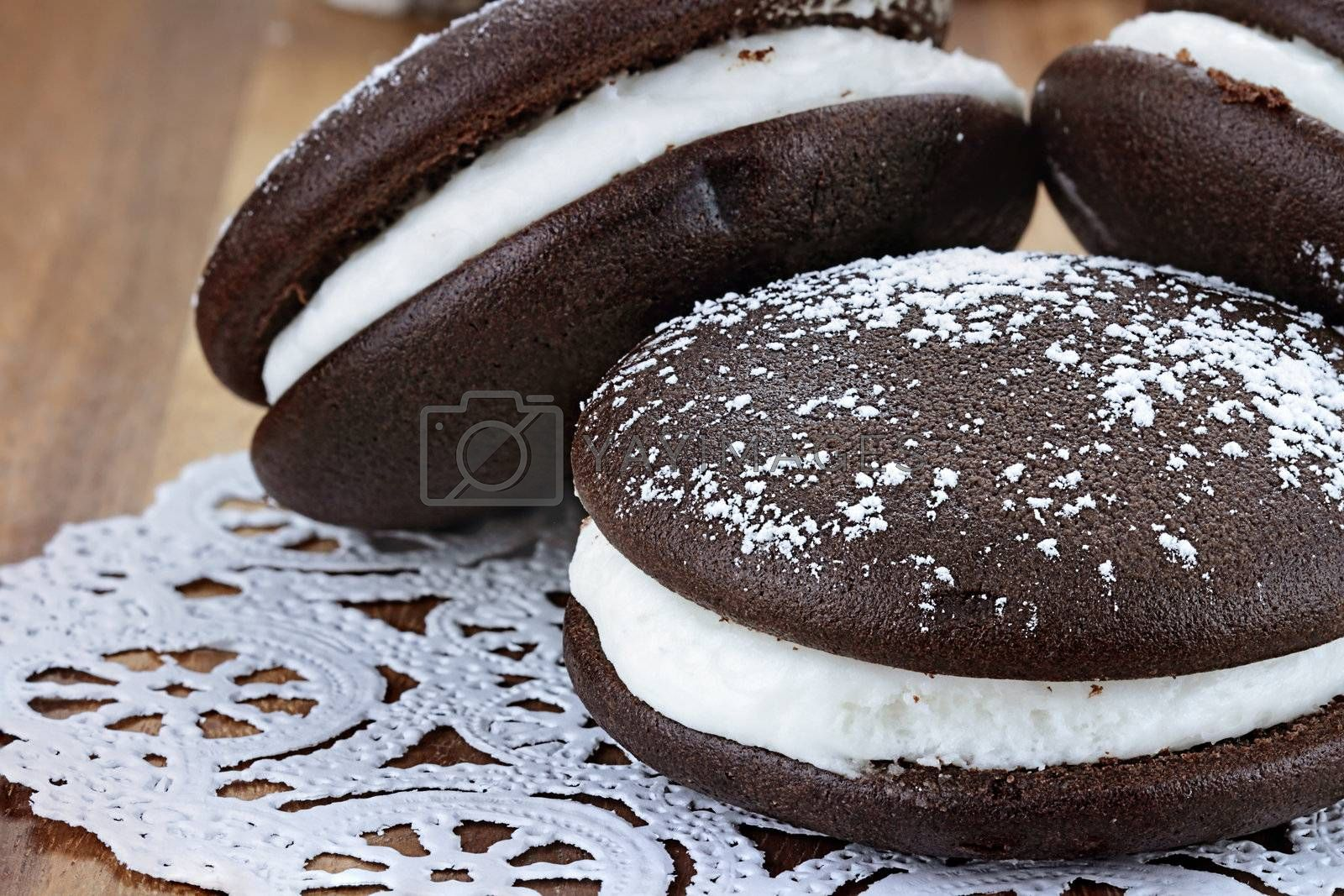 Macro image of three whoopie pies or moon pies with powdered sugar. Shallow depth of field.