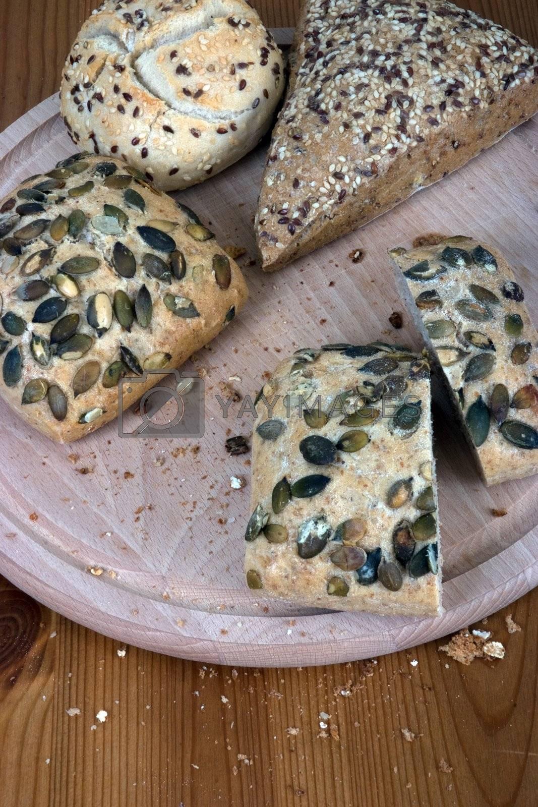 A group of multi-grain bread, on a chopping board