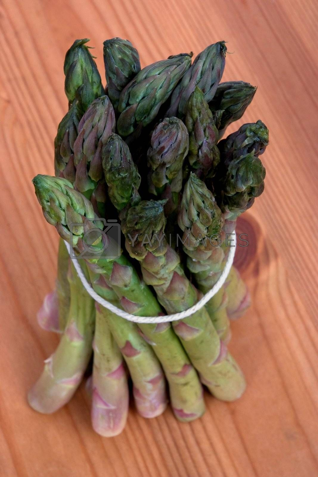 A bundle of asparagus tied up on a wooden work surface