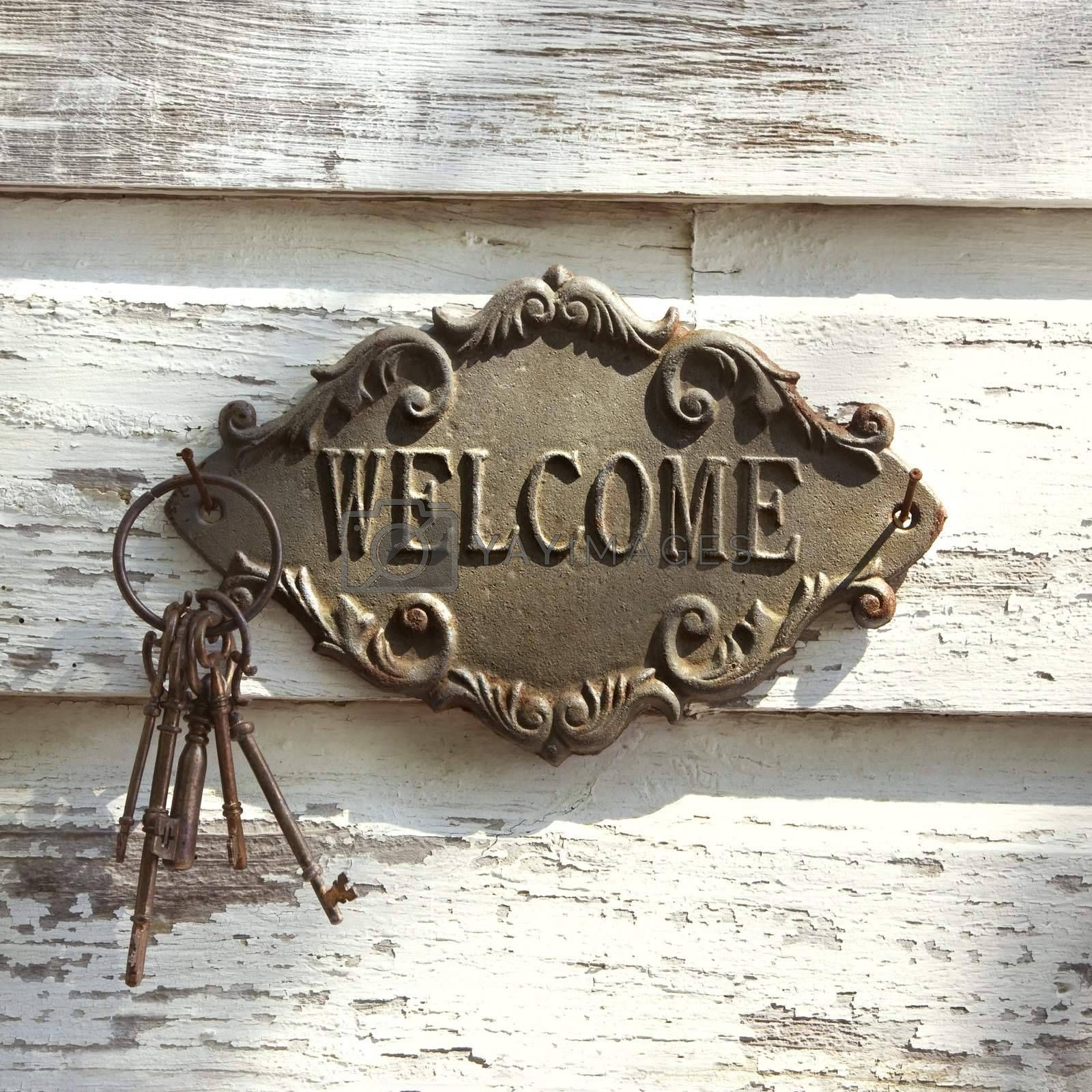 Welcome sign and metal keys on old white peeling building.
