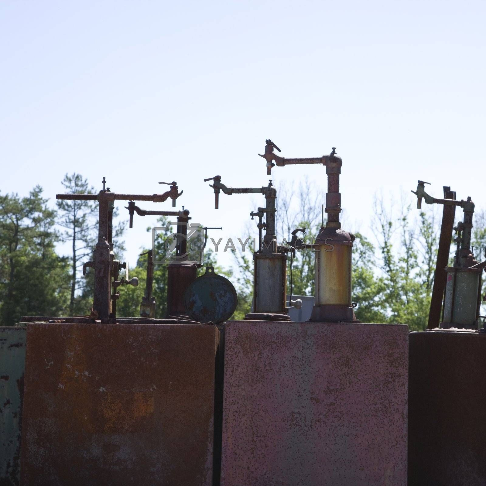 Old rusted metal machinery silhouetted against sky.