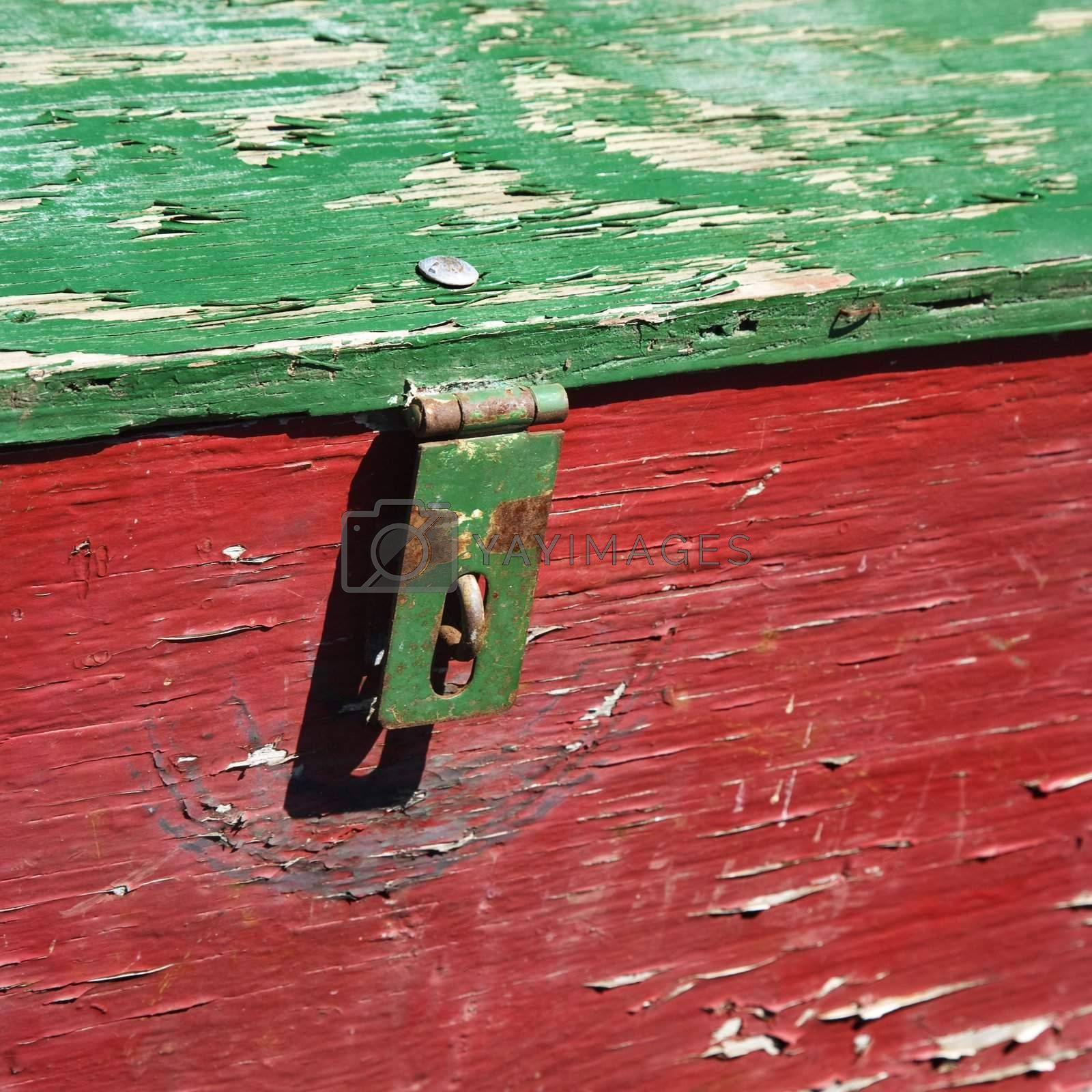 Old red and green weathered wooden storage container.