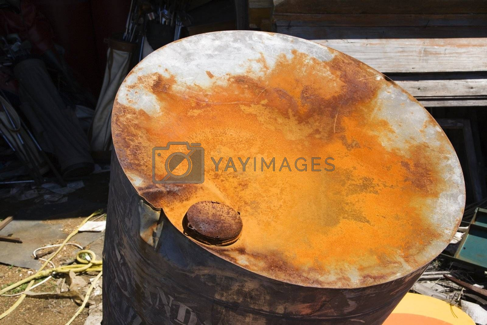 Old weathered oil barrel with rusty top.