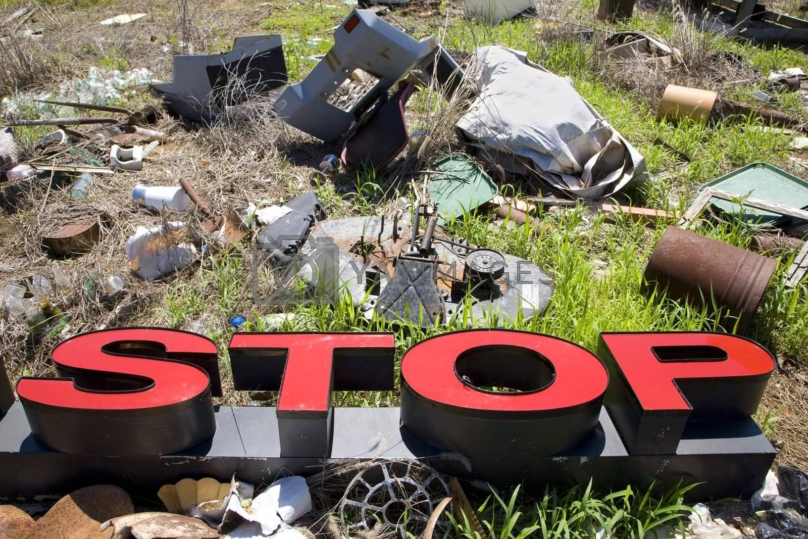 "Word ""STOP"" lying amongst junk and garbage."