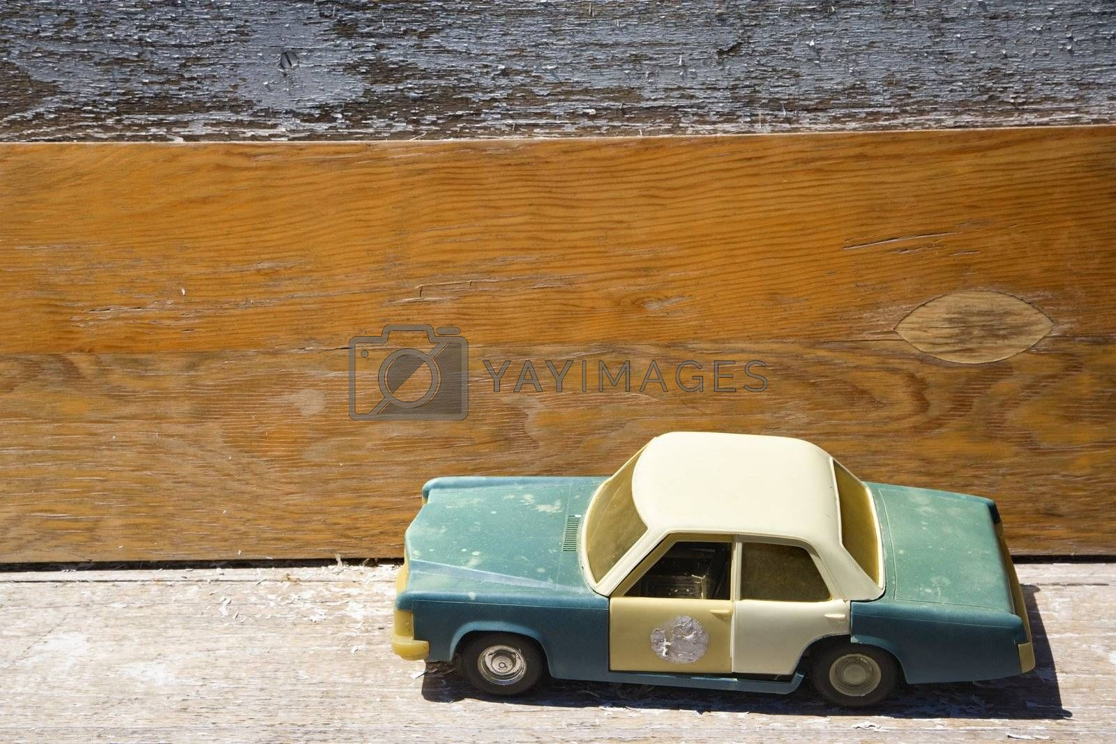 Toy police car on wooden shelf.