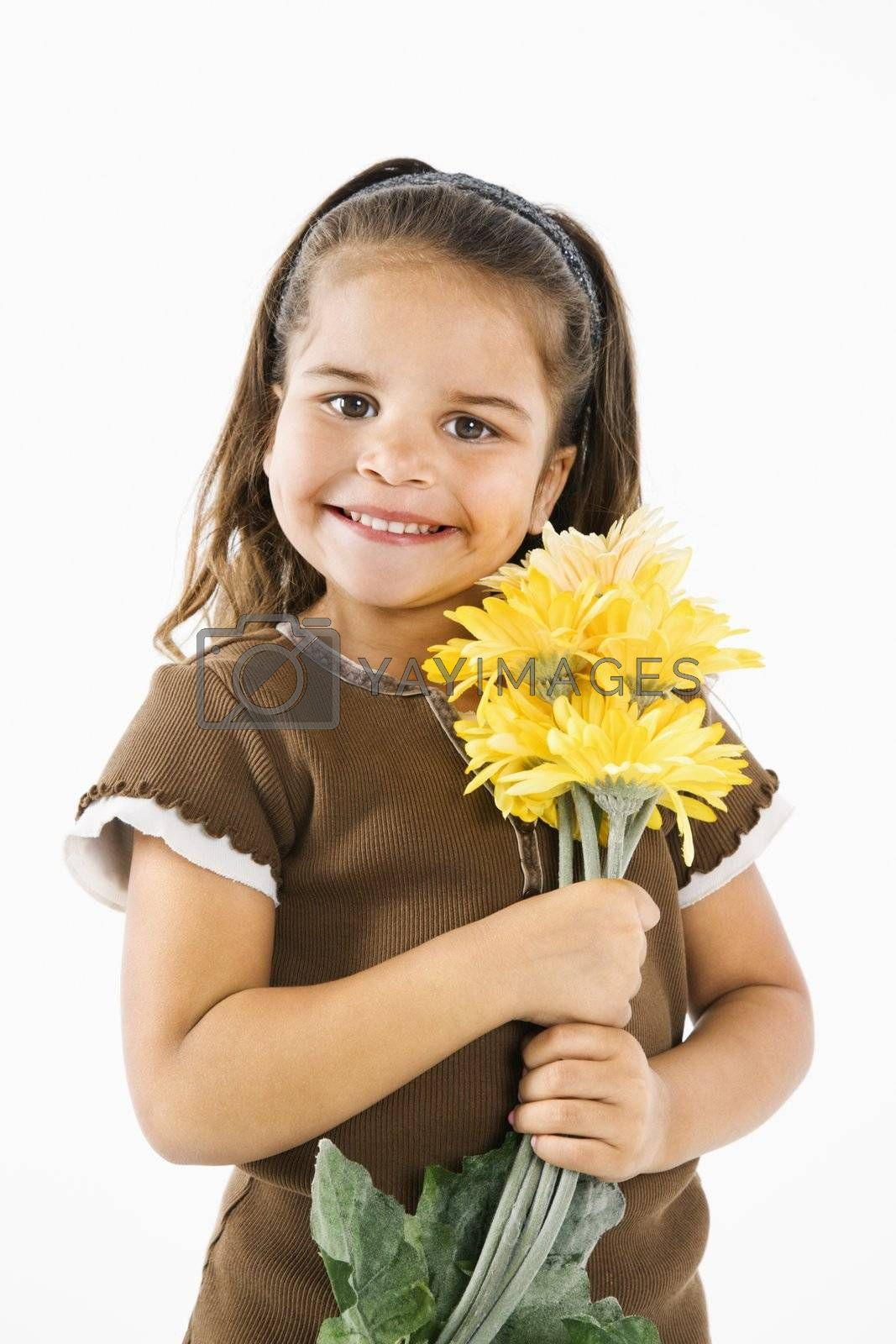Cute little hispanic girl holding bouquet of yellow flowers.
