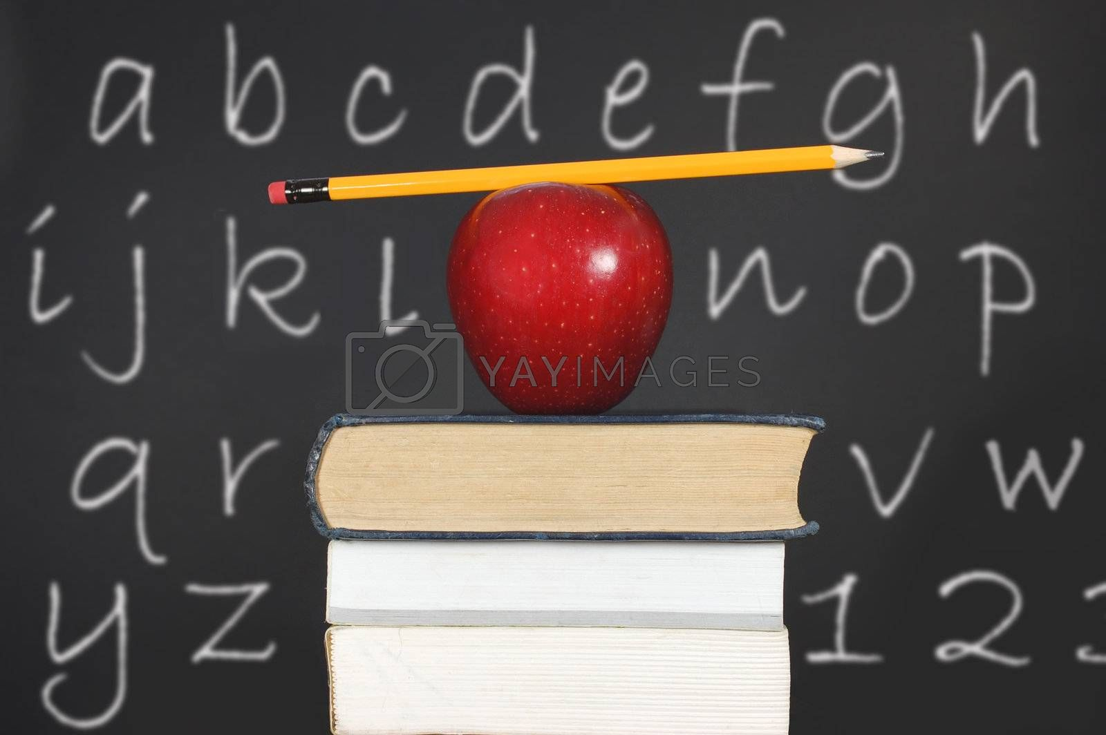 Pencil balancing on an apple and a stack of books