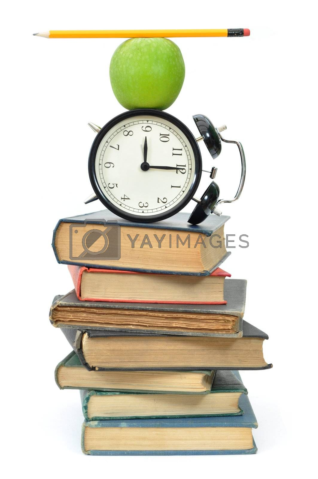 Balancing act of objects, including an apple and closk, on top of a stack of books