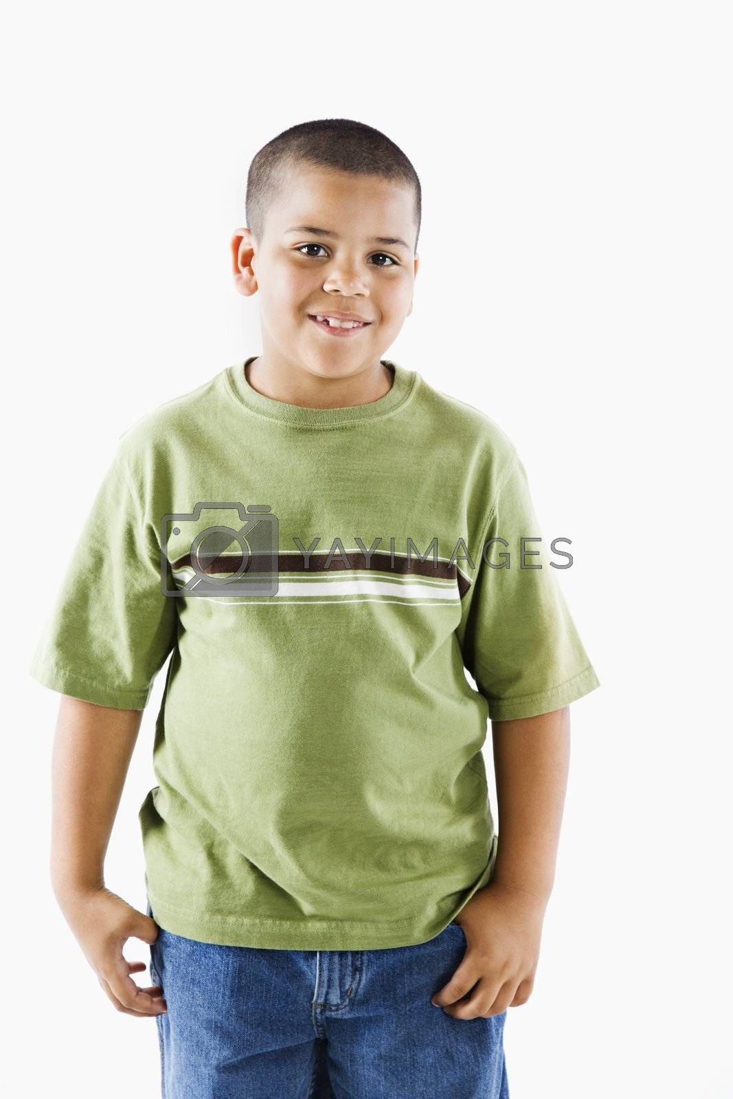 Young latino adolescent boy standing smiling.
