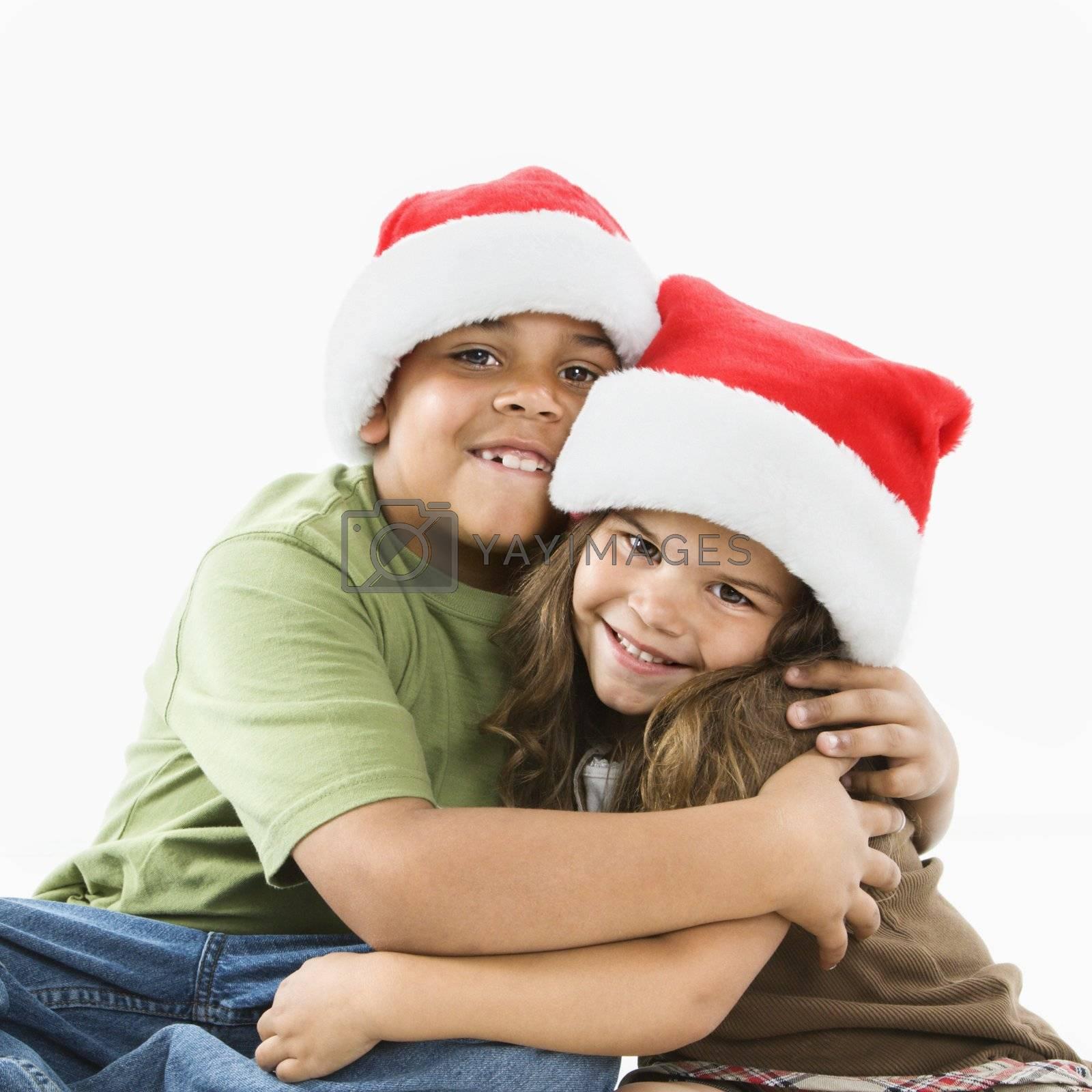 Hispanic brother and sister wearing santa hats hugging