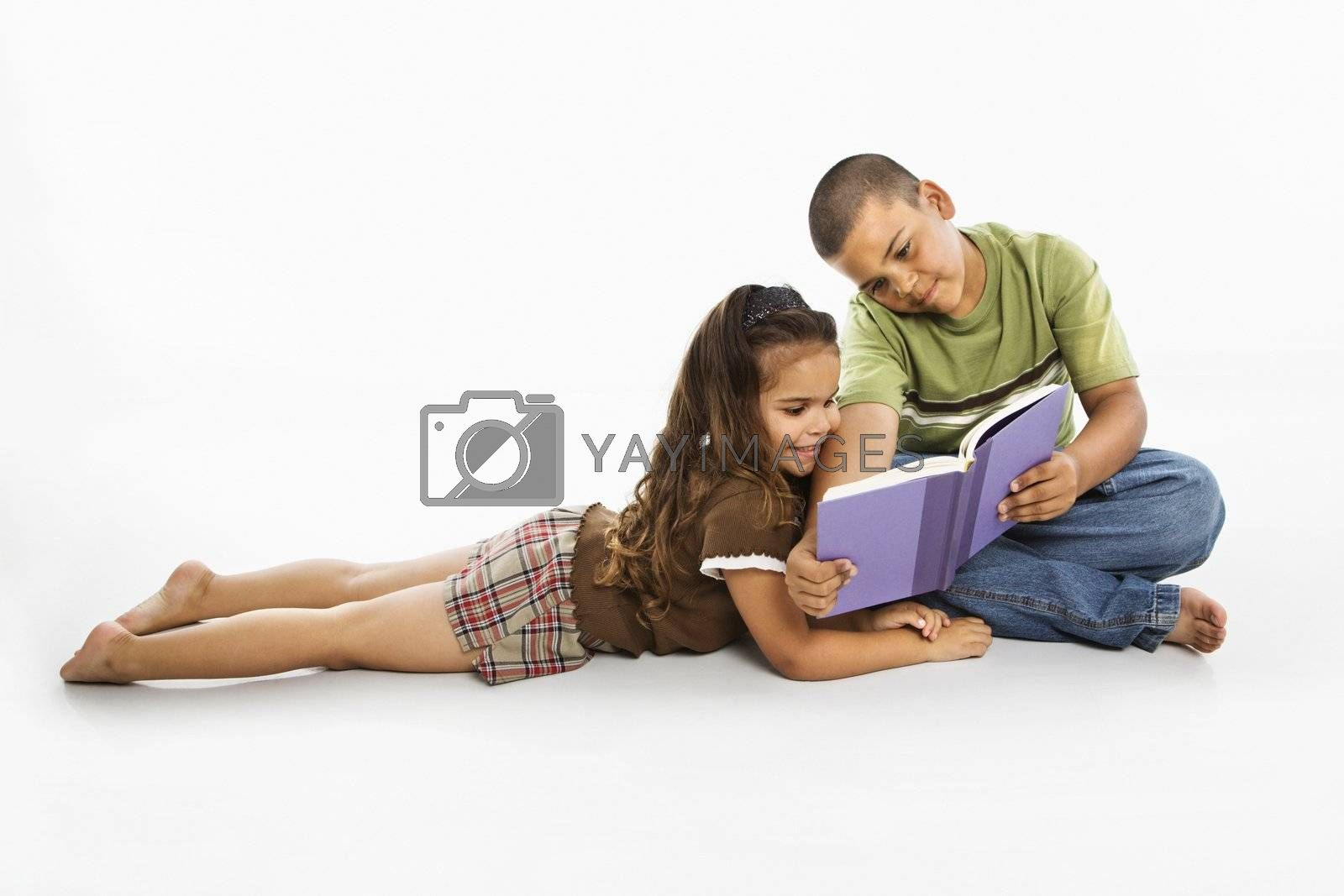 Brother and sister reading book together.
