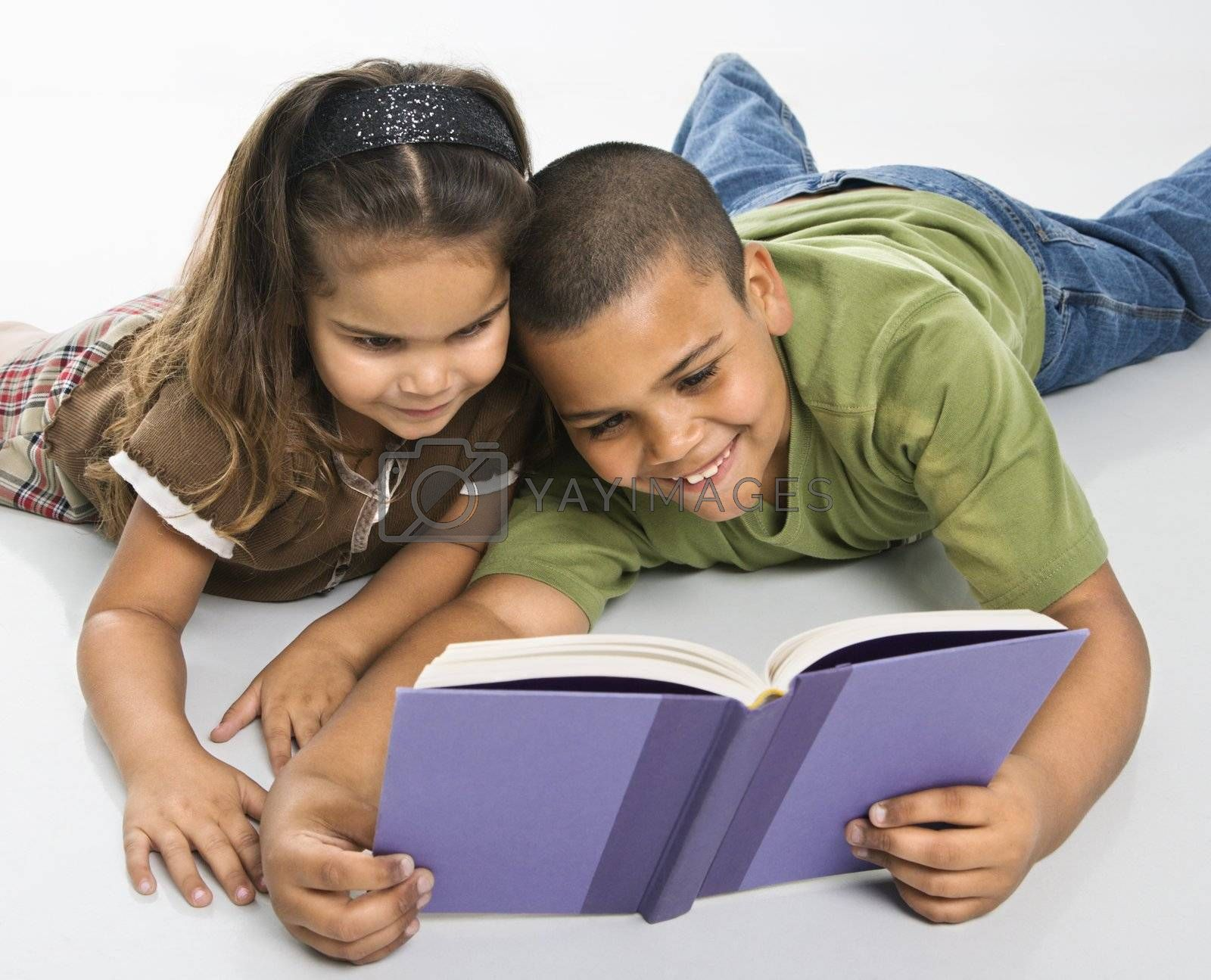 Hispanic brother and sister reading book together sitting on floor.