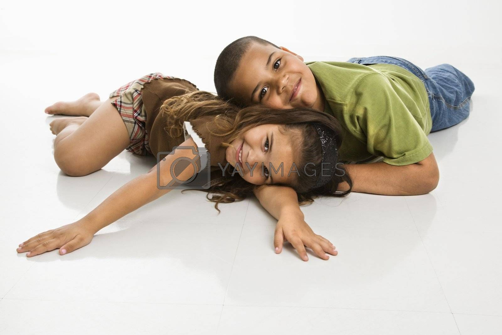 Portrait of Hispanic brother and sister lying on floor smiling at viewer.