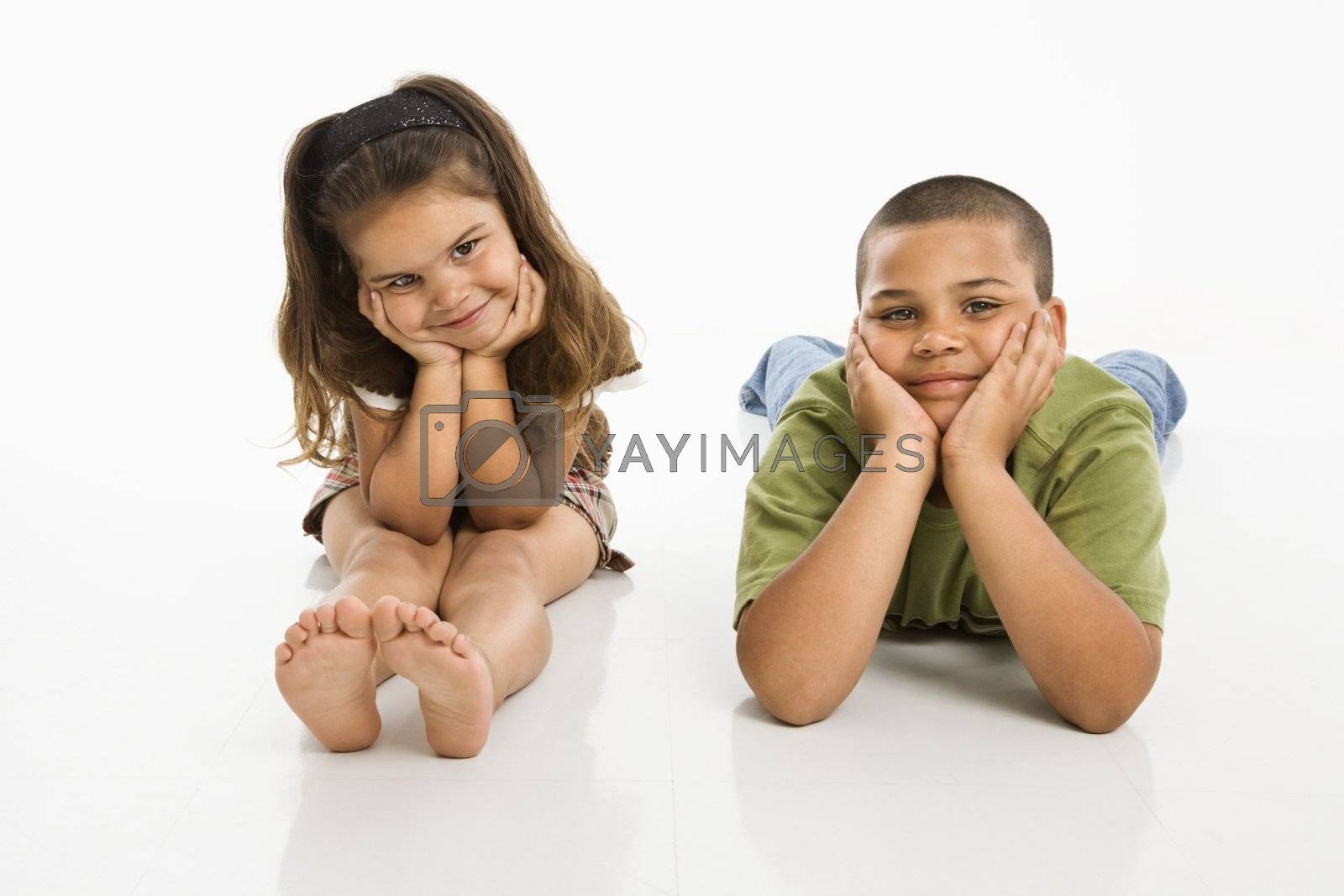 Hispanic brother and sister sitting smiling at viewer.