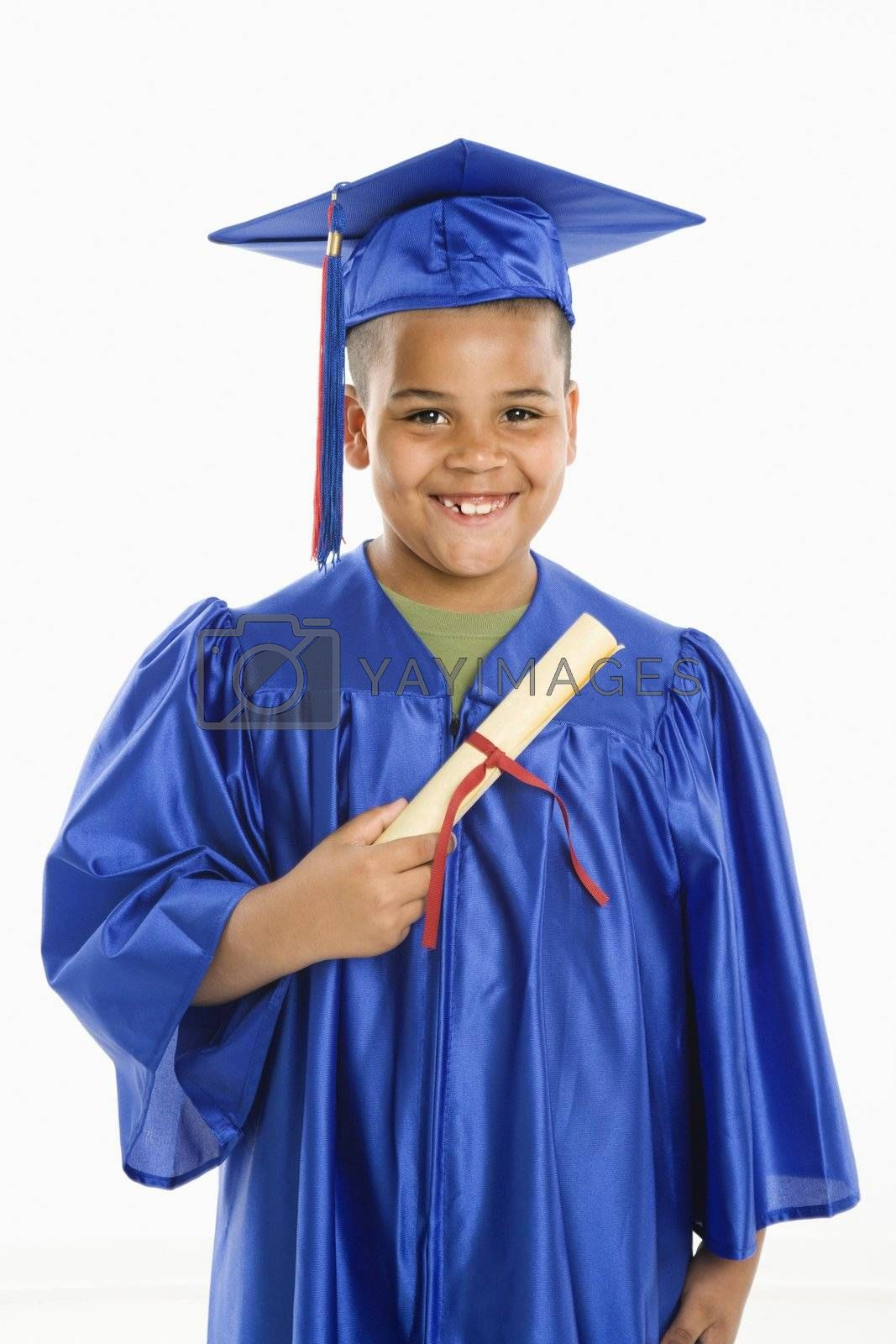 Young boy wearing blue graduation gown holding diploma.