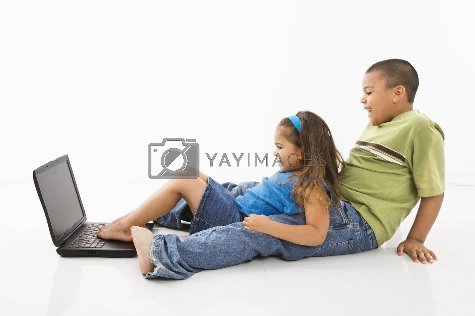 Brother and sister putting feet on laptop computer and smiling.