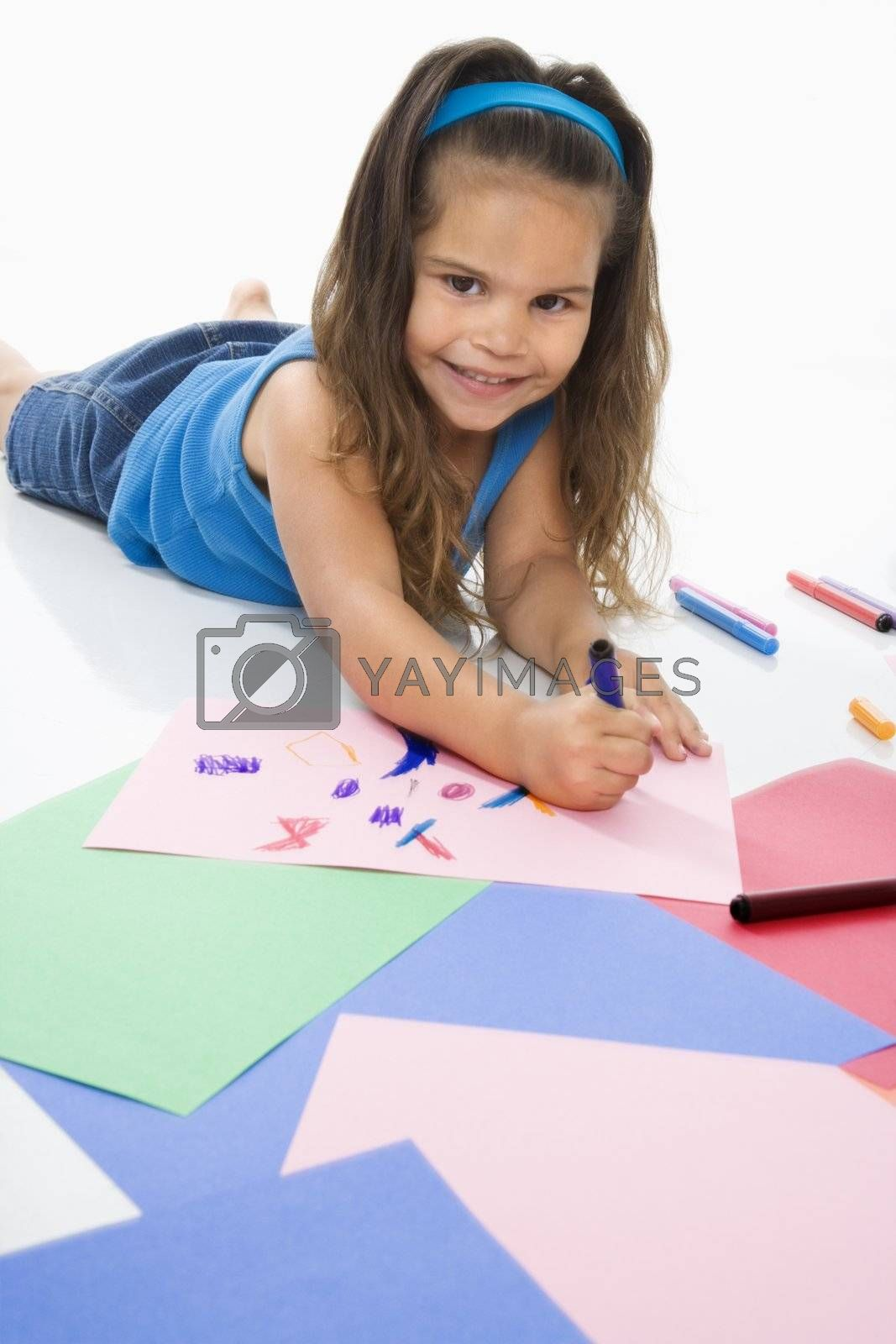Young latino girl coloring on construction paper and smiling.