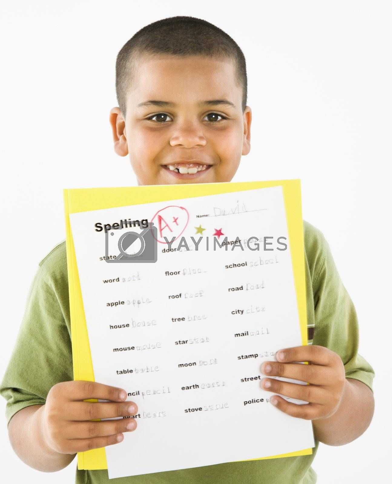 Young boy proudly showing paper with A+ grade.