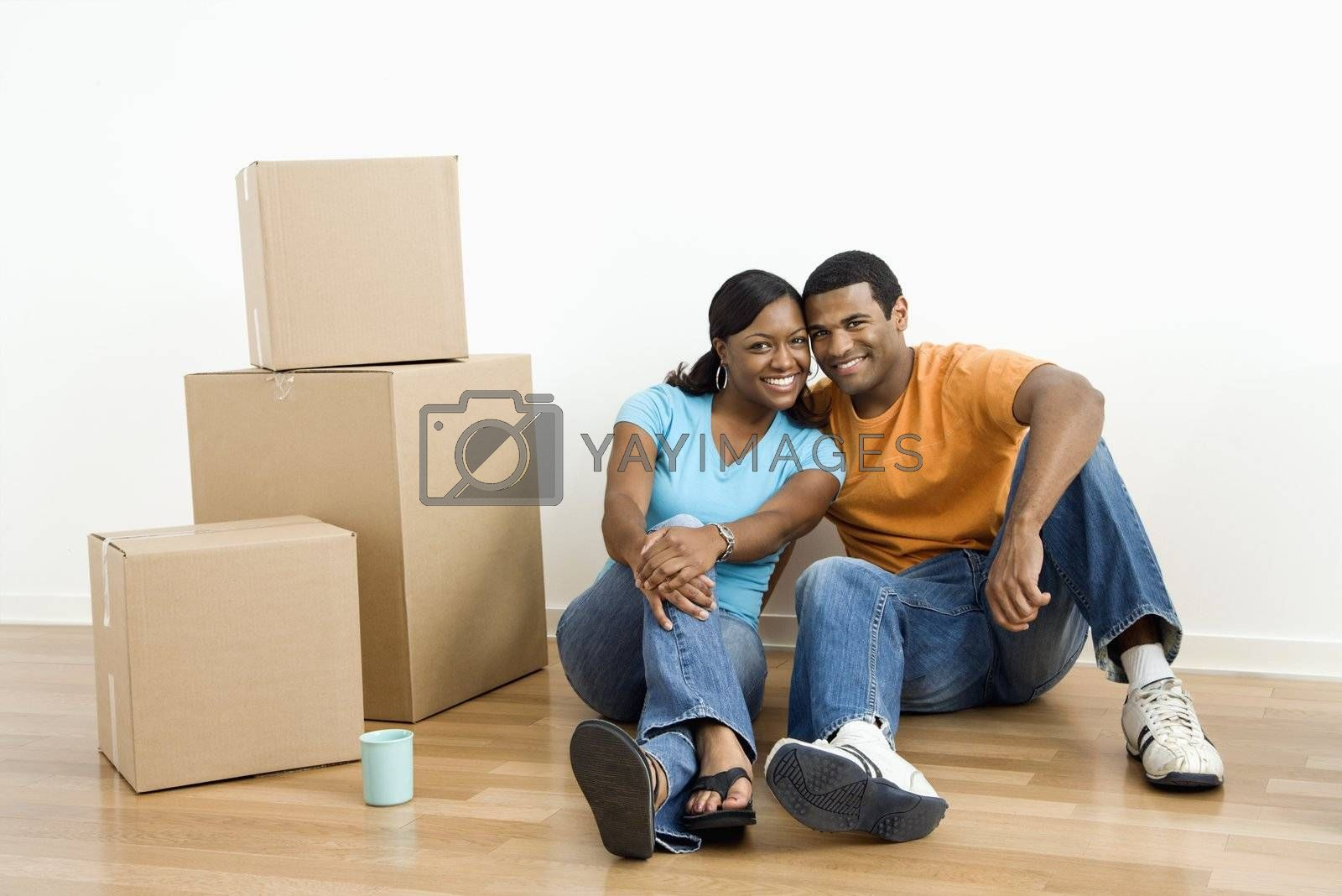 African American male and female couple sitting on floor next to moving boxes.