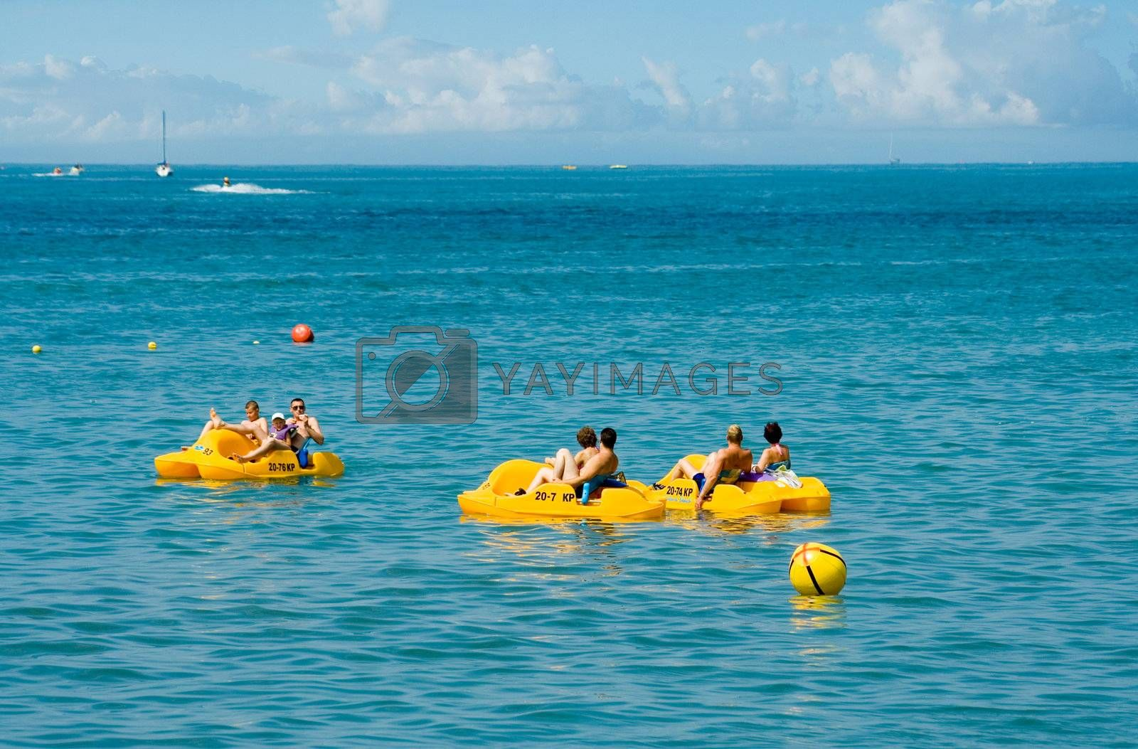 people in a yellow pedal boat  close to beach