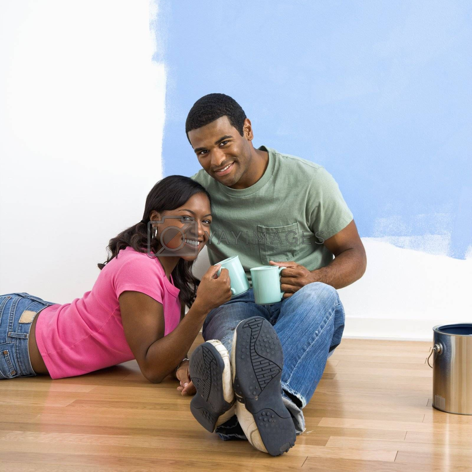 African American couple relaxing together with coffee next to half-painted wall.