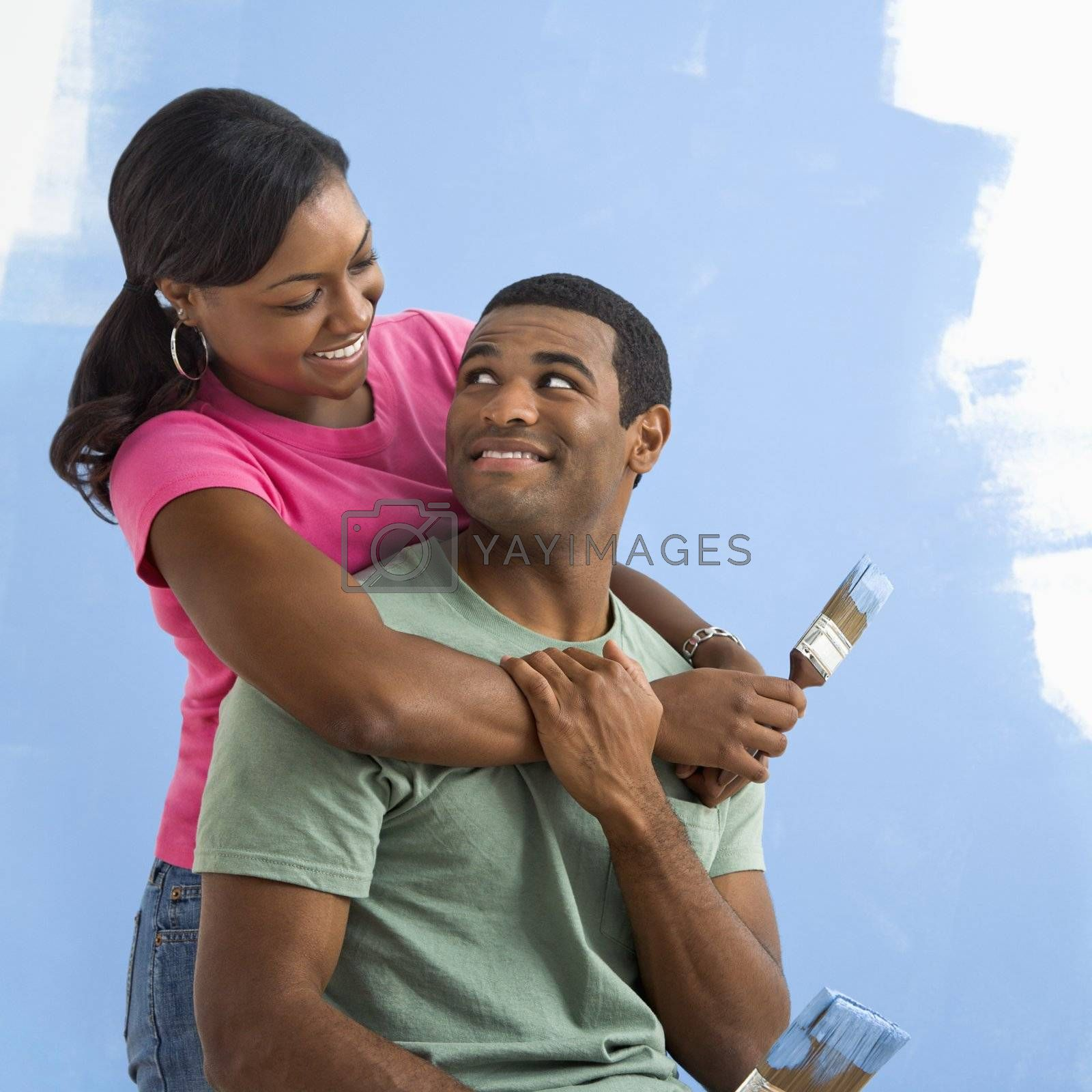 Portrait of African American male and female couple next to half-painted wall.