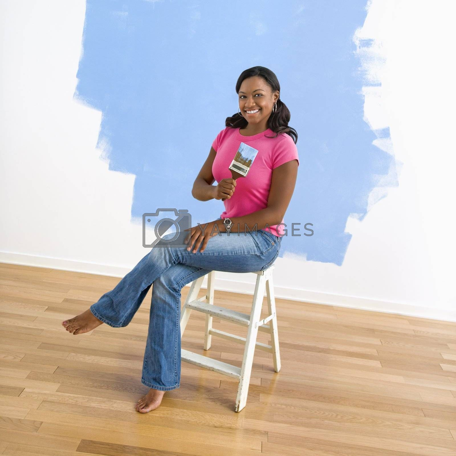 African American young woman sitting next to half-painted wall with paintbrush.