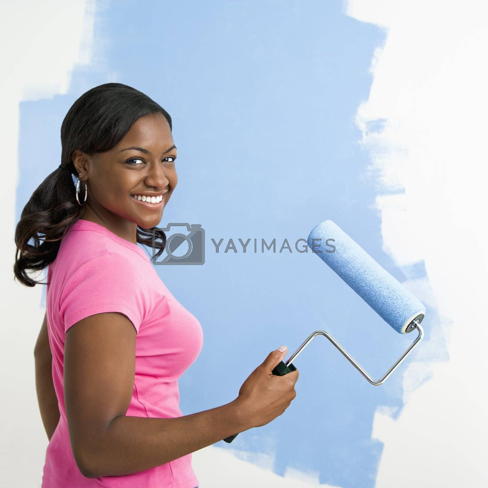 African American woman painting wall blue smiling at viewer.