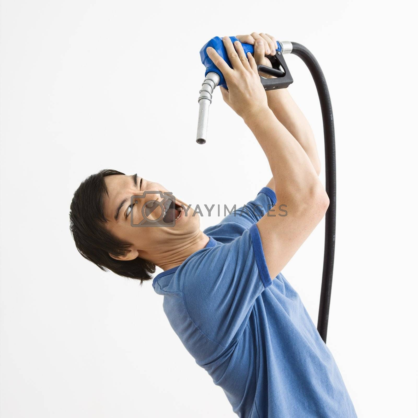Asian young man fighting with gasoline pump nozzle.