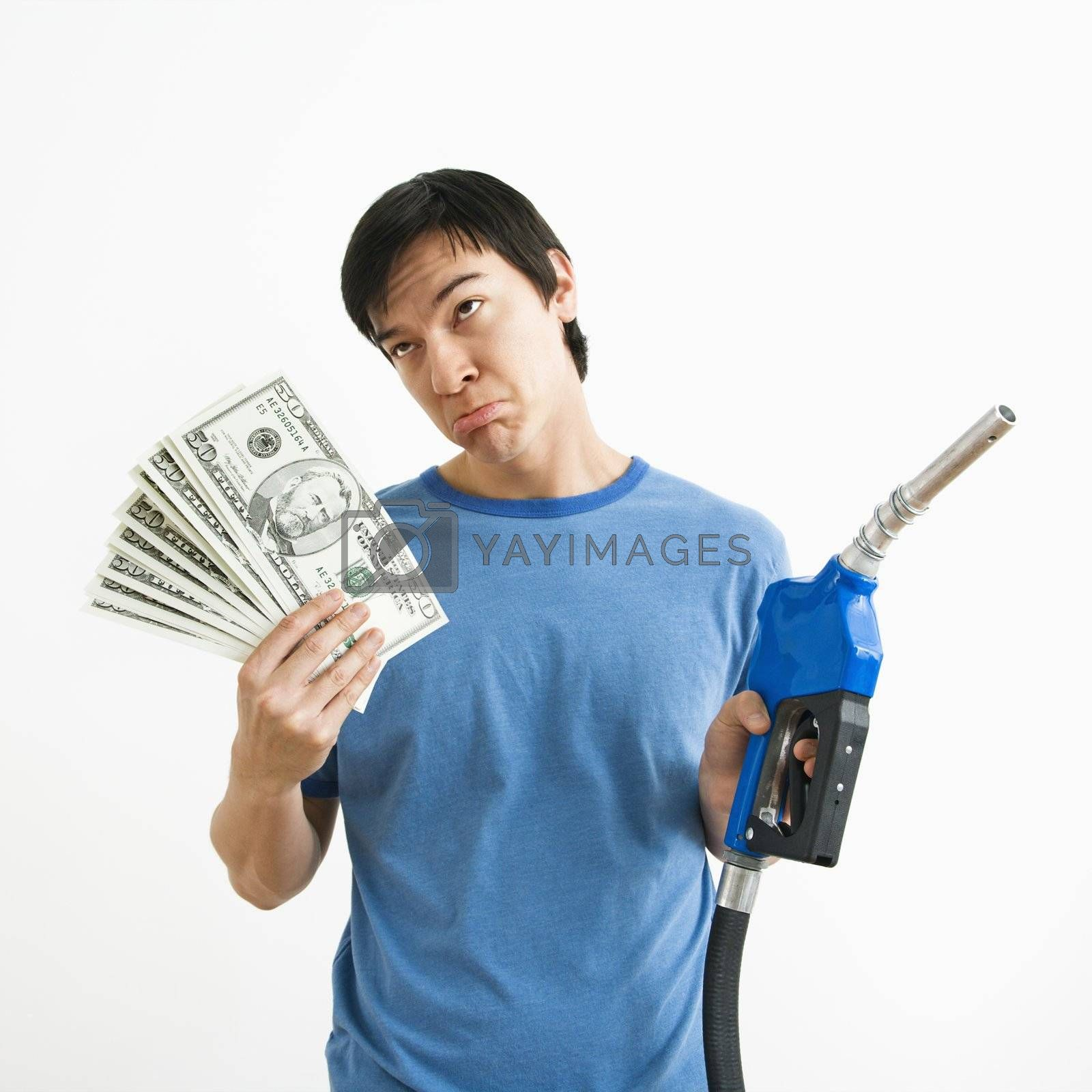 Asian young man with sad expression holding money and gas pump nozzle.