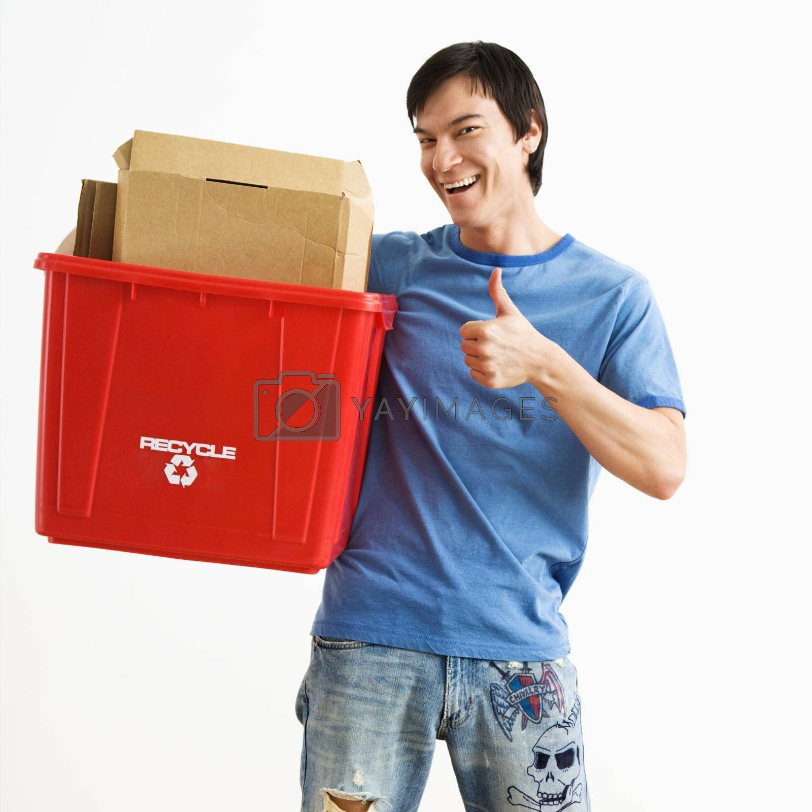 Portrait of smiling Asian young man standing holding recycling bin.