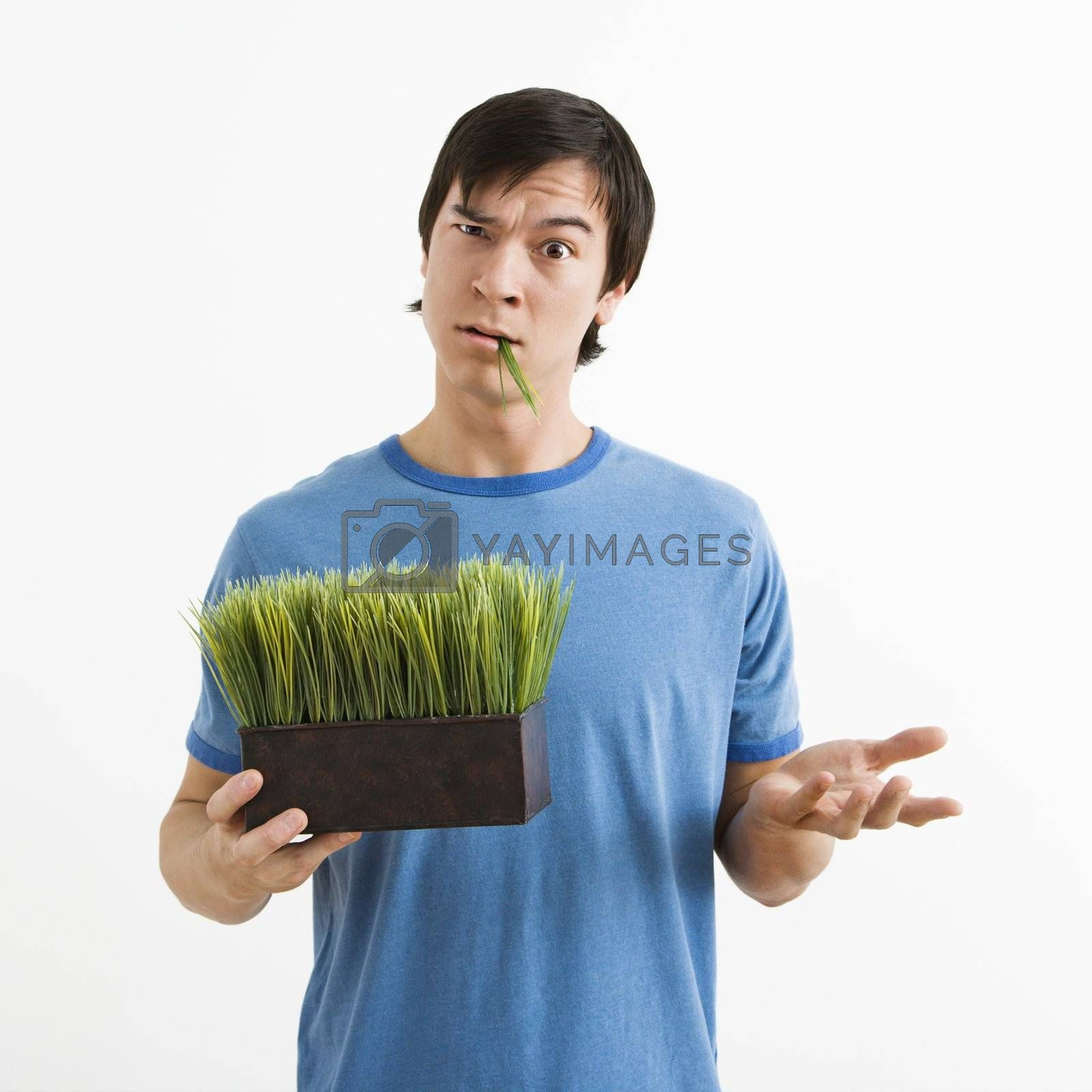Portrait of Asian young man standing holding pot of grass.