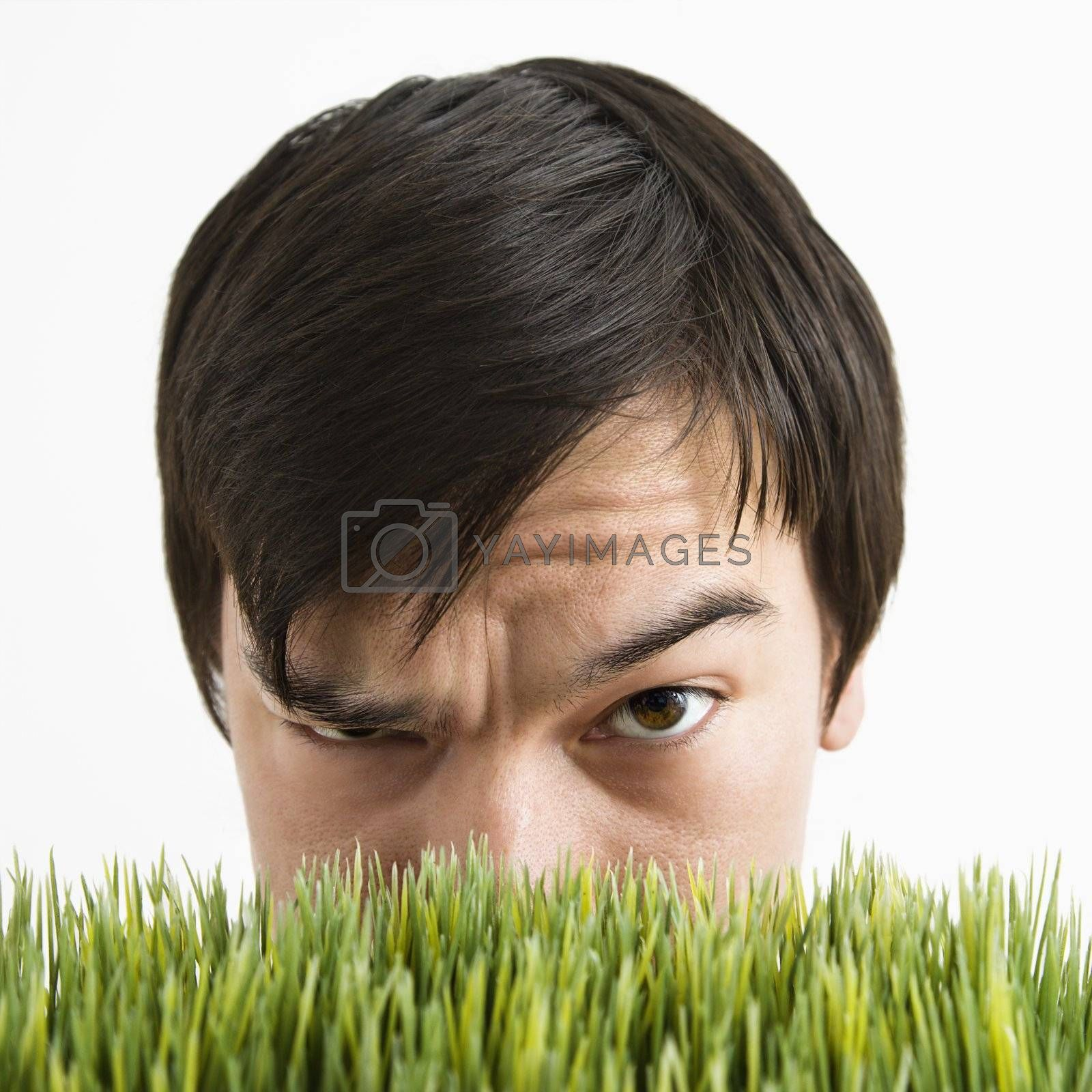 Asian young man looking over grass with eyebrow cocked.