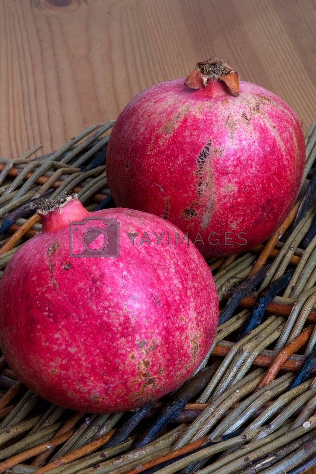 Two Pomegranites on a wicker plate