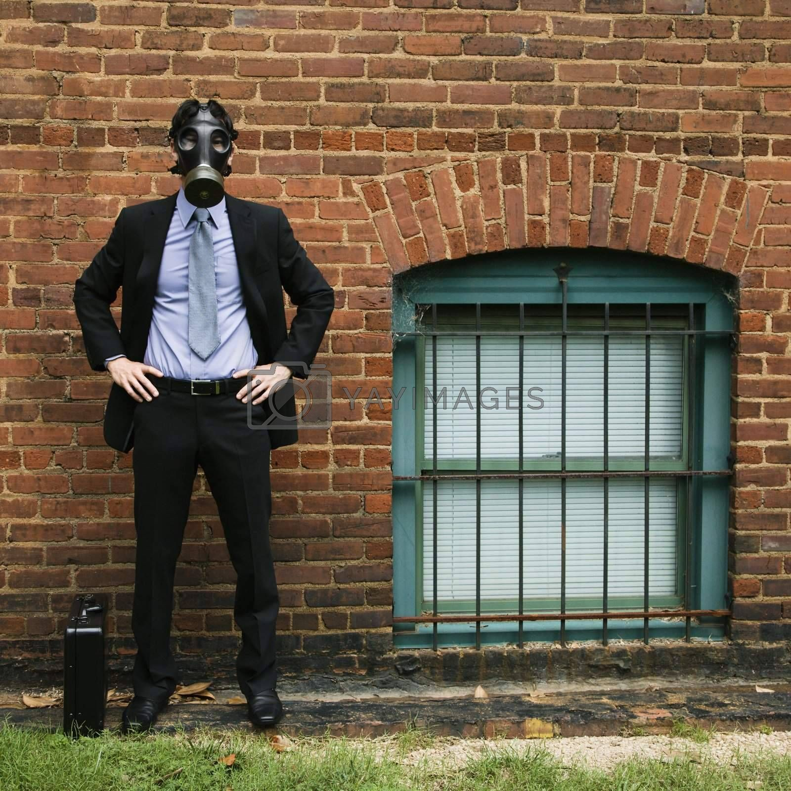 Businessman standing next to brick wall wearing gas mask.