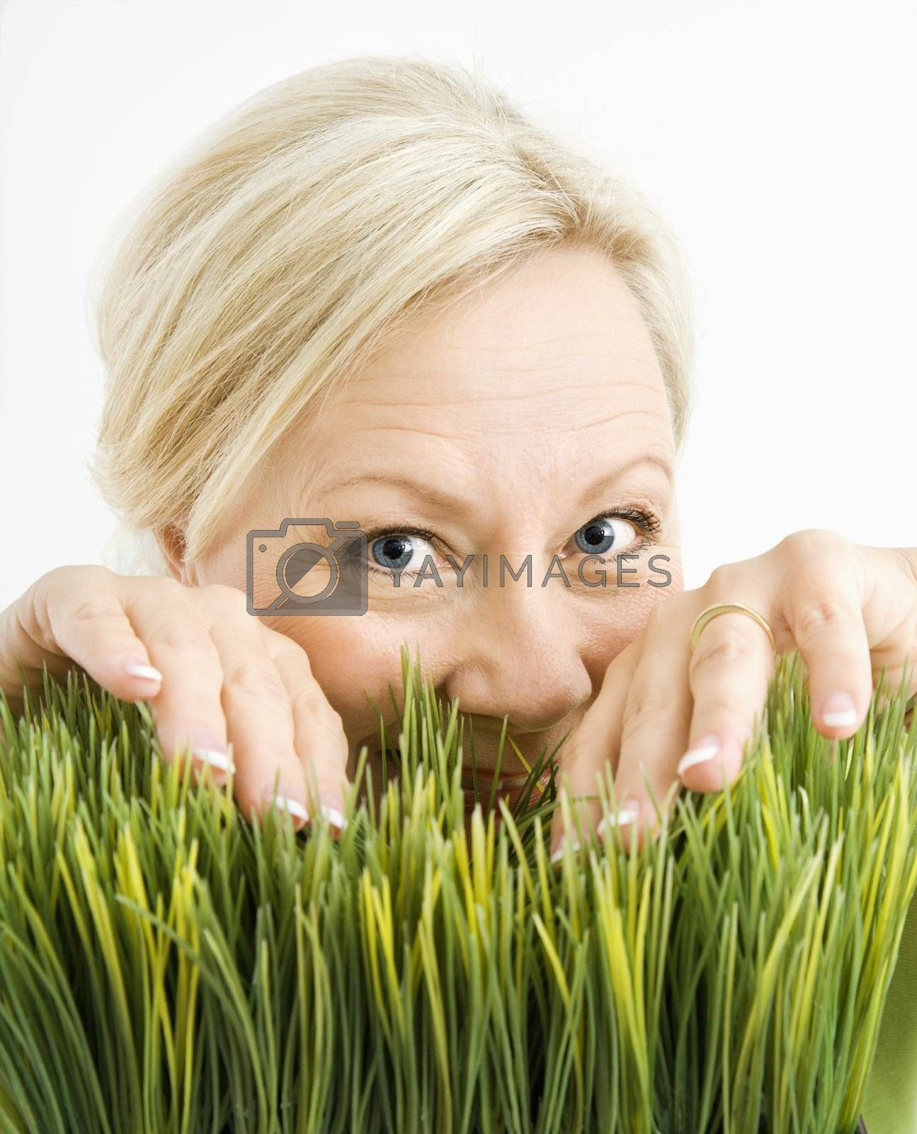 Portrait of adult blonde woman looking through grass at viewer.